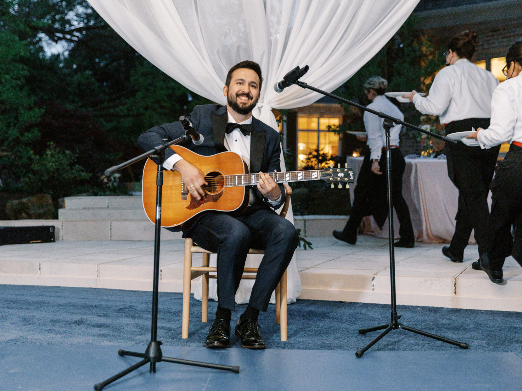 groom smiling during guitar reception performance