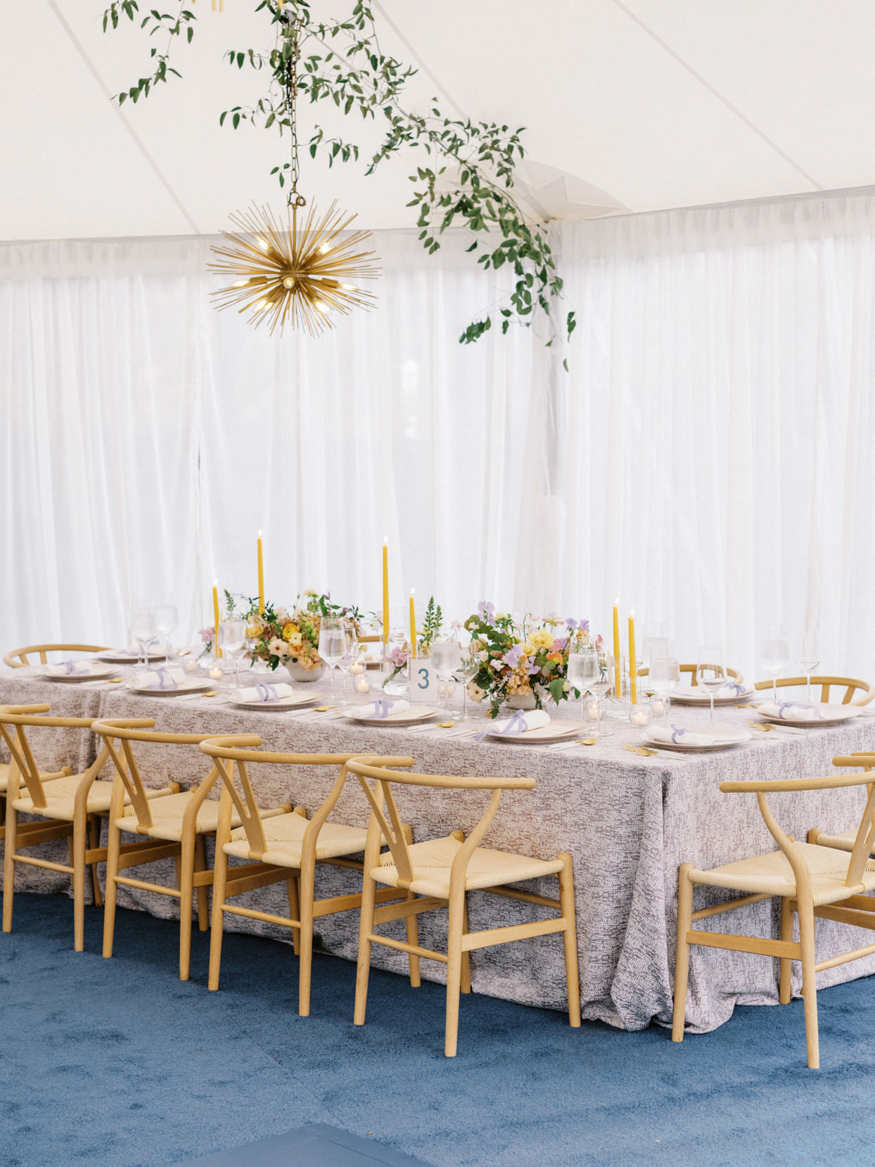 long wedding reception table with light wooden chairs