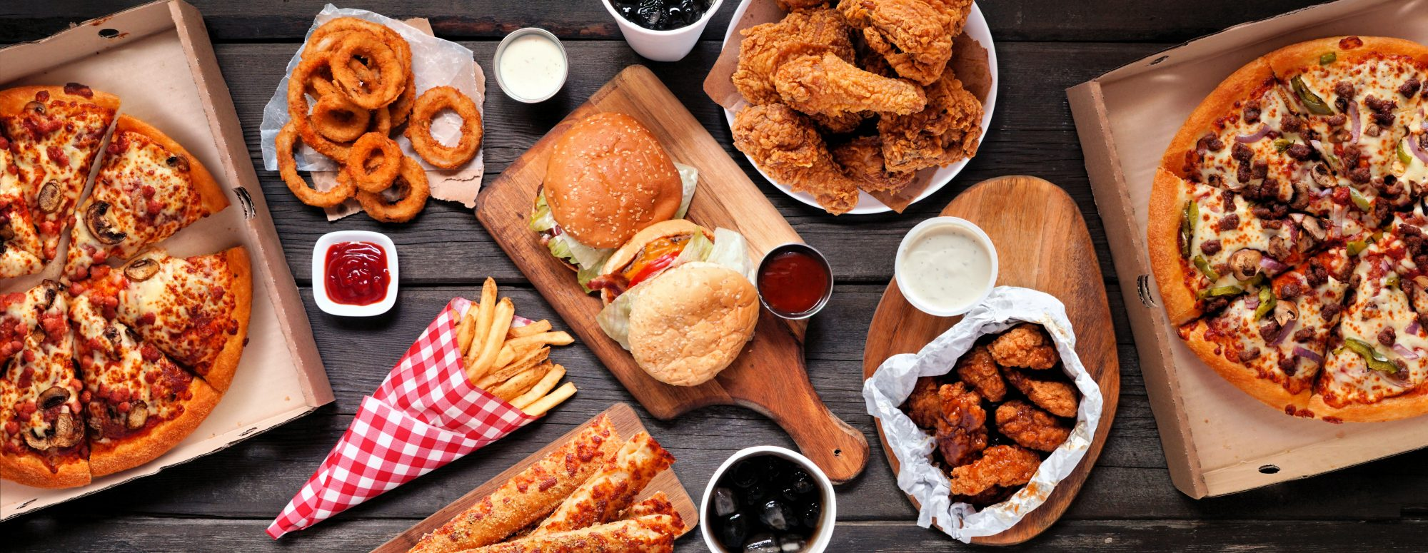assorted take out junk food on wood table
