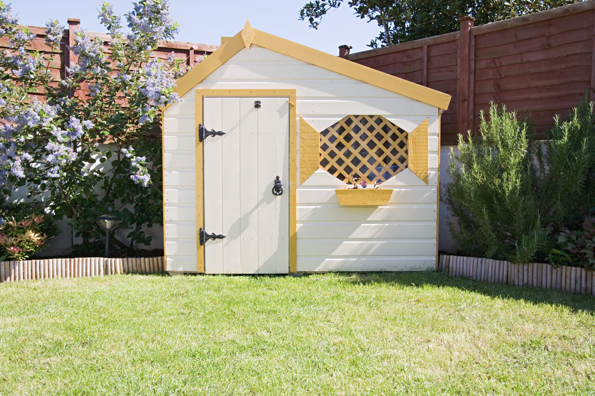 white and yellow painted garden shed