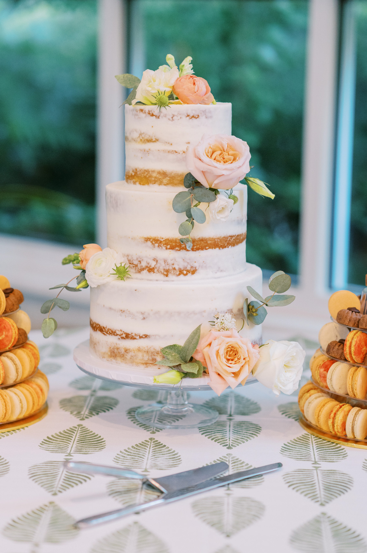 three tiered white frosted wedding cake with orange floral decor