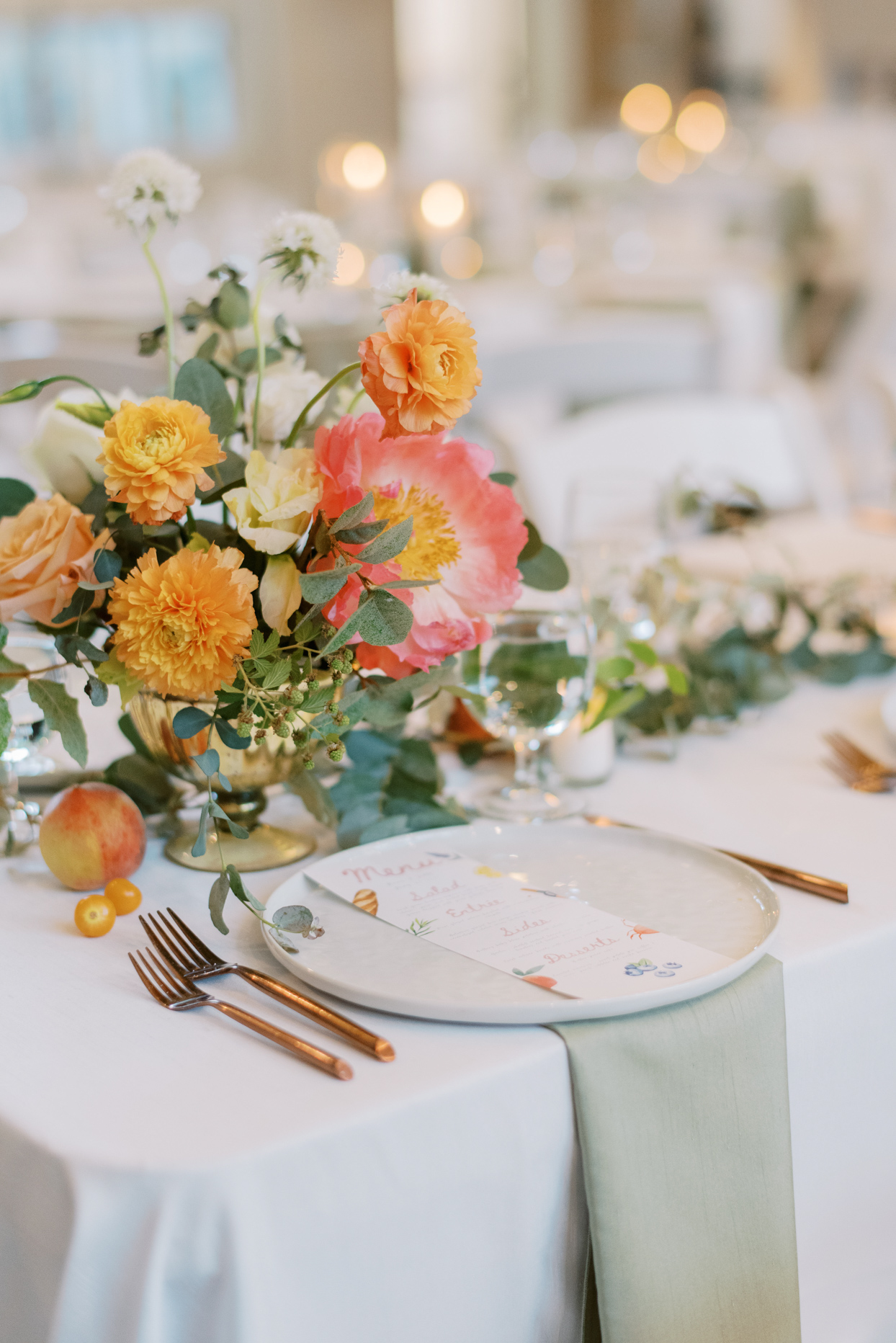 orange floral wedding reception centerpieces with green place settings