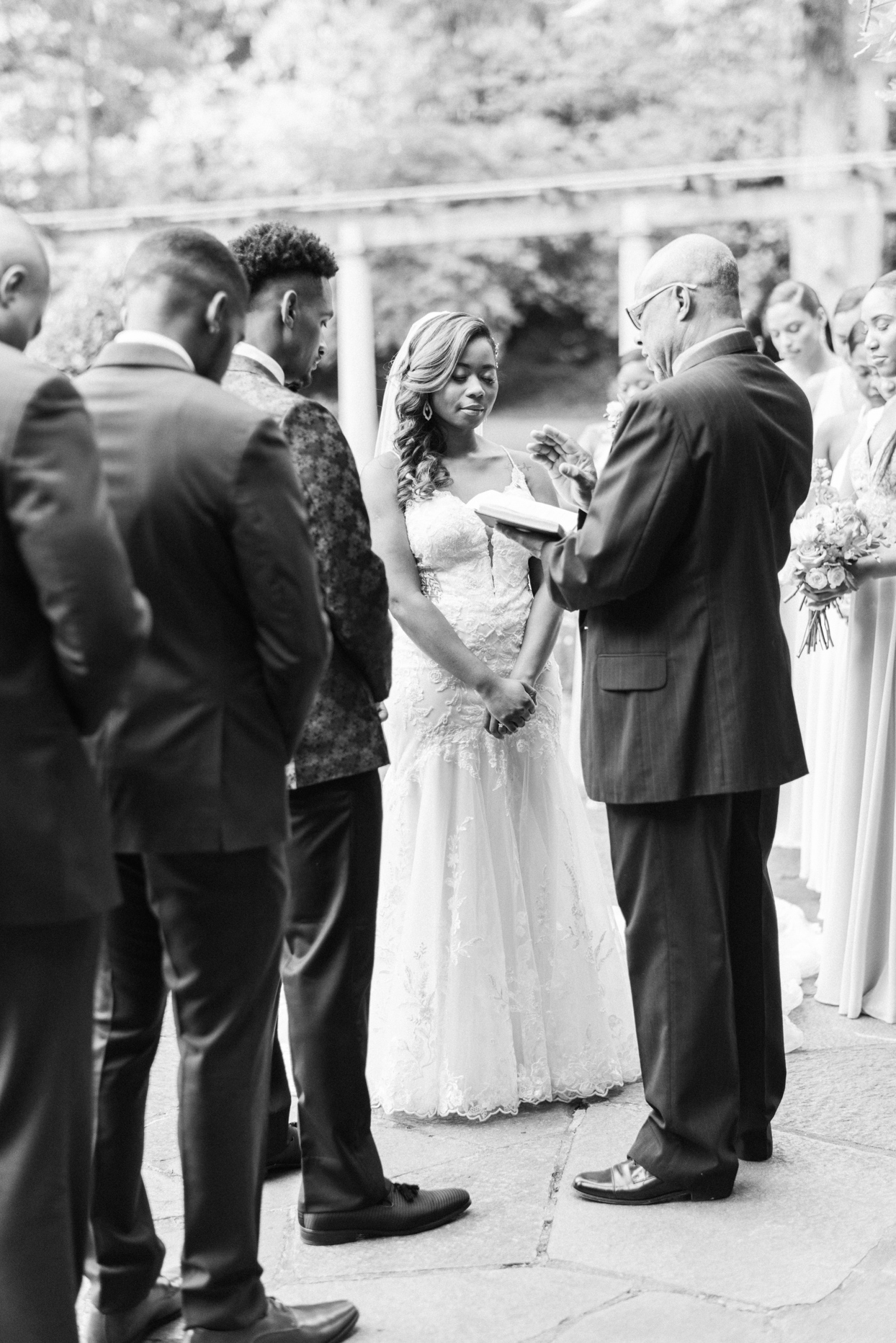 bride and groom surrounded by wedding party during ceremony