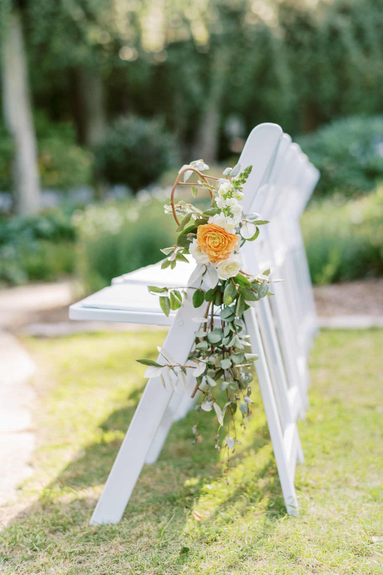 greenery and flowers hanging from aisle chair