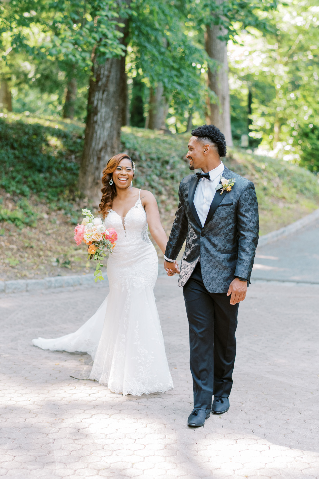 bride smiling at groom holding hands on stone pathway