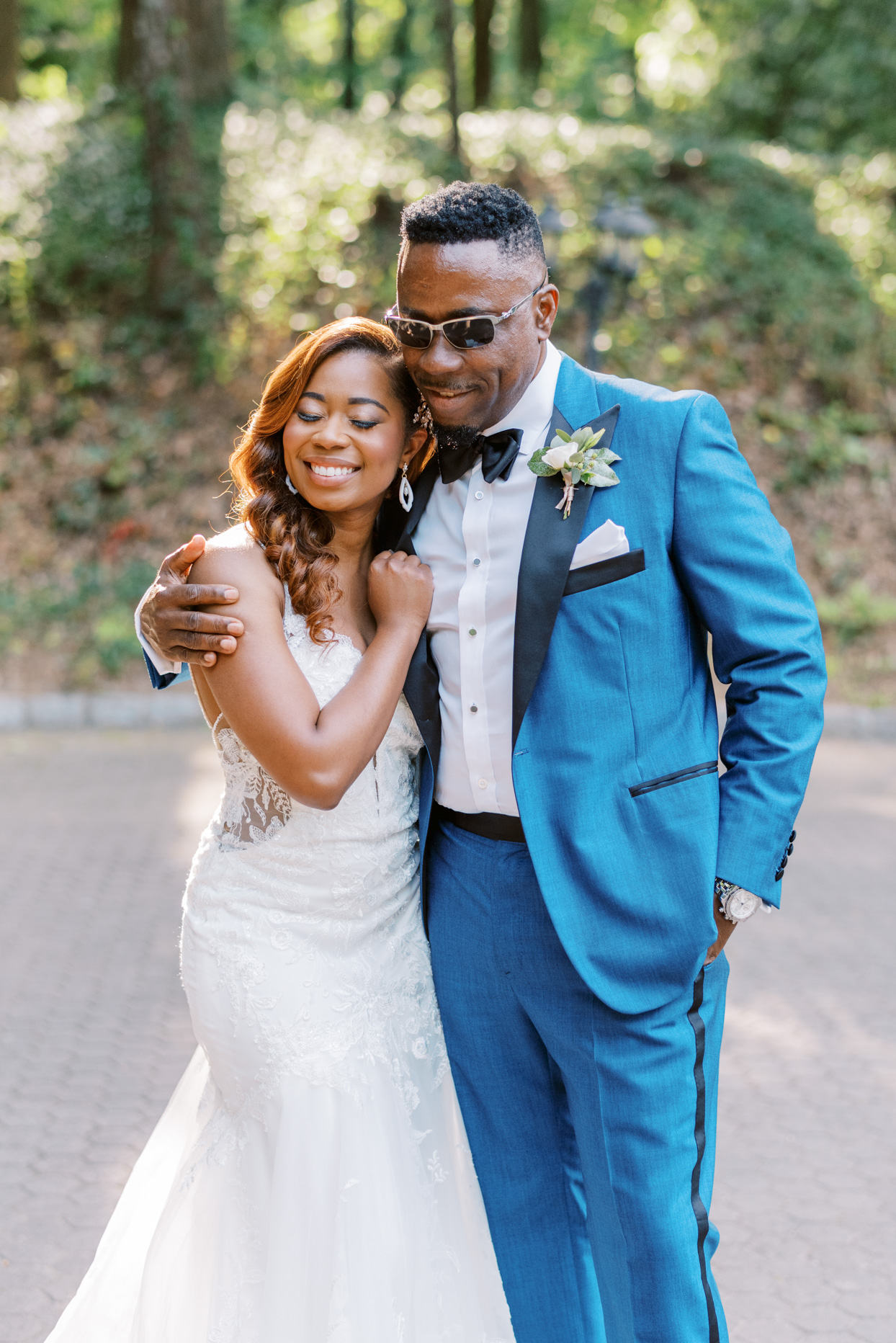 bride smiling with dad wearing blue suit and sunglasses