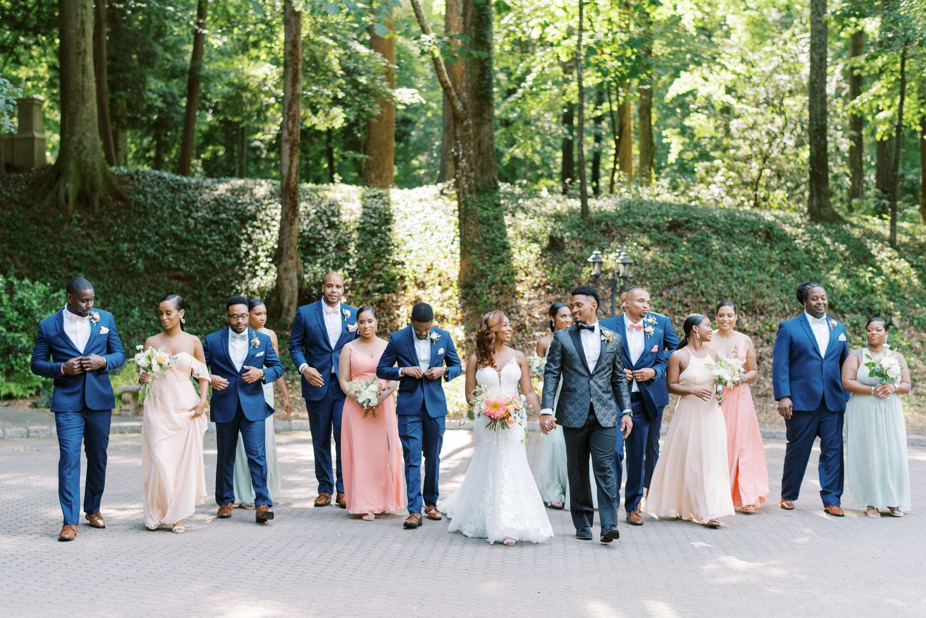 bride and groom walking with wedding party outside