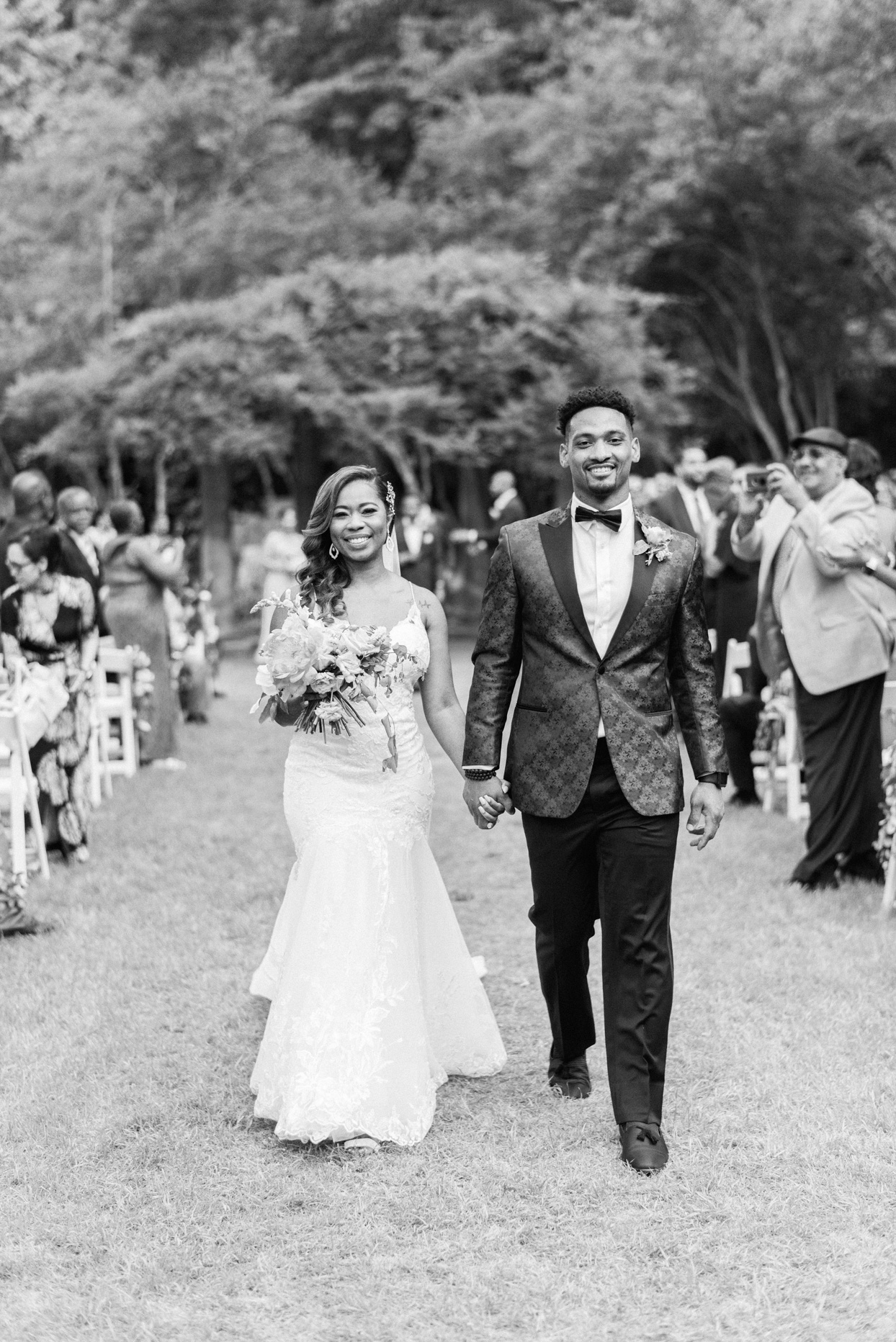 bride and groom during recessional smiling holding hands