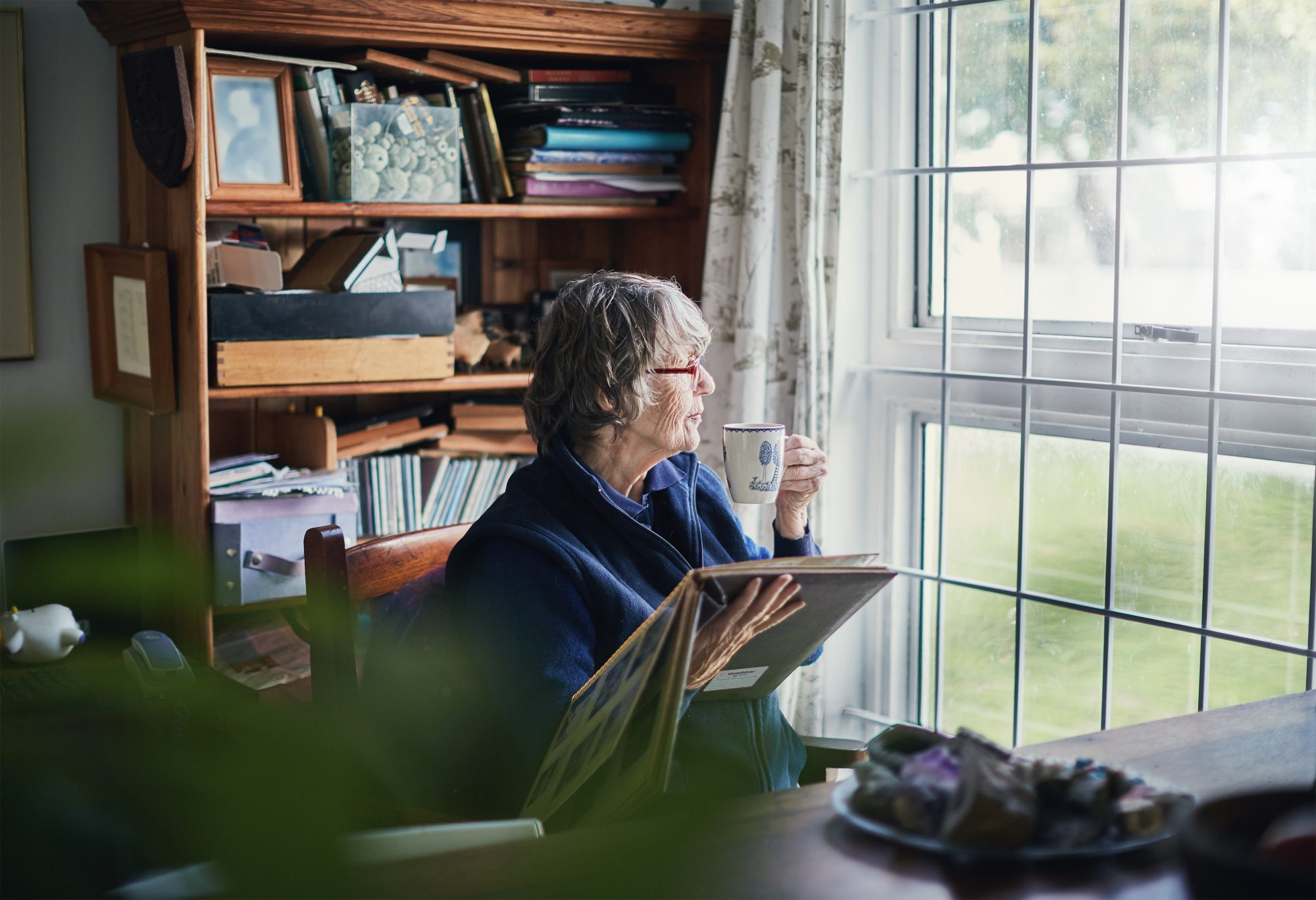 senior woman alone in room looking at photo album