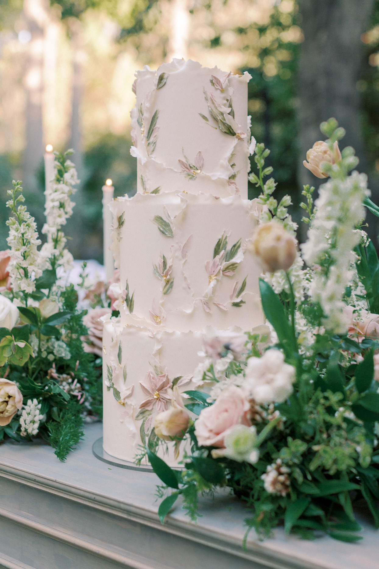 three-tiered wedding cake with frosting flowers