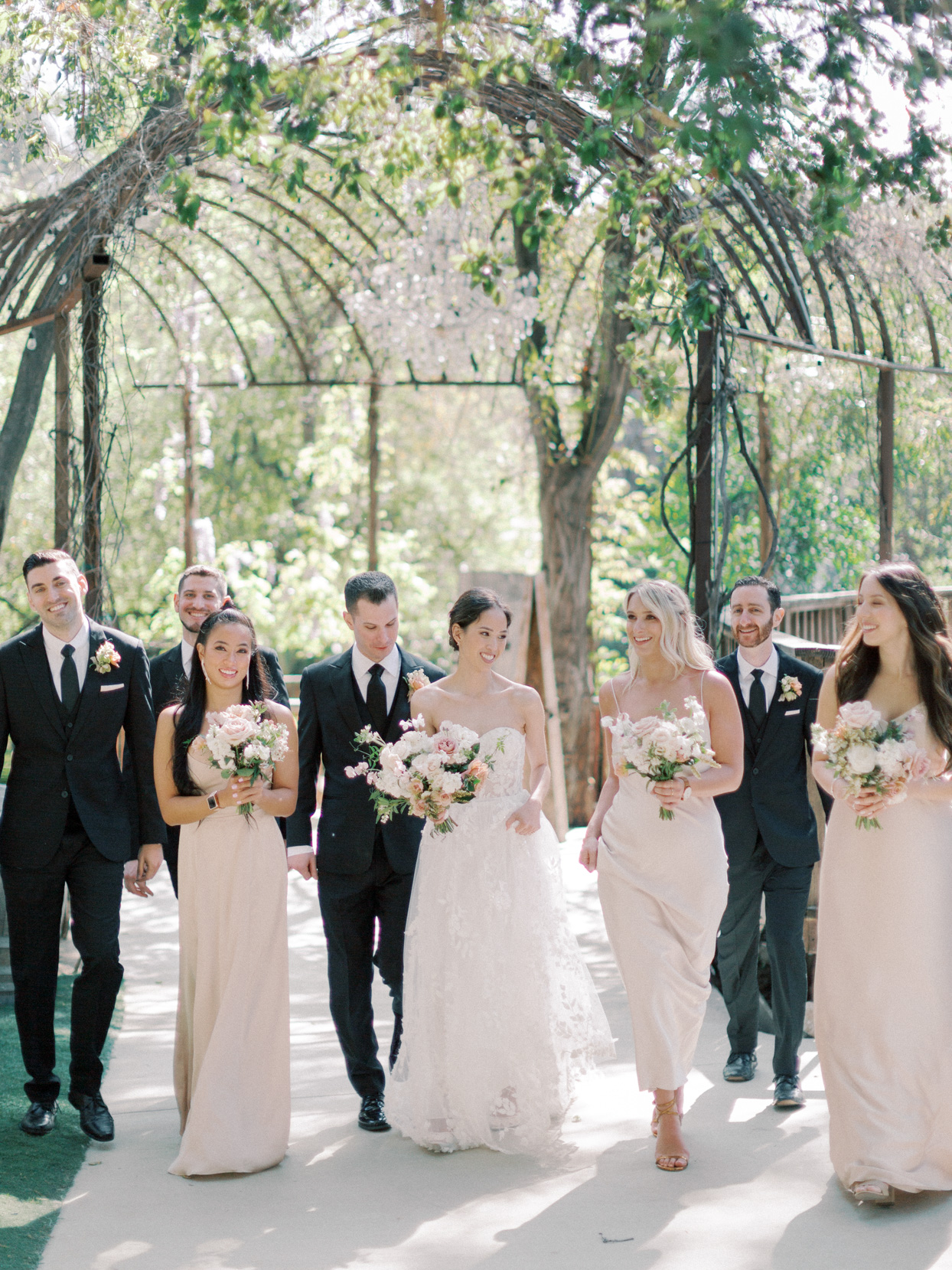 wedding party in suits and beige colored dresses