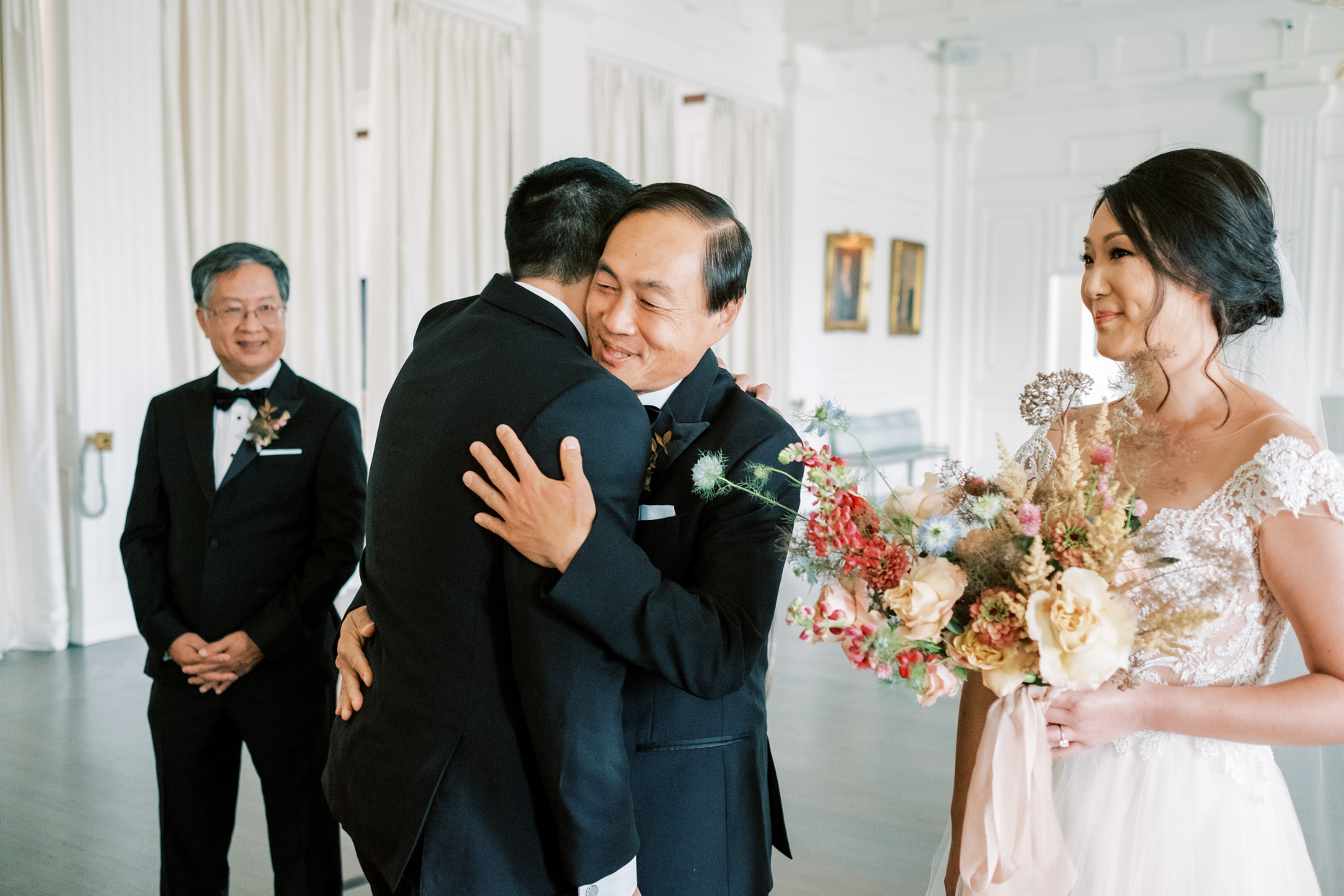 bride's father and groom embrace at the altar