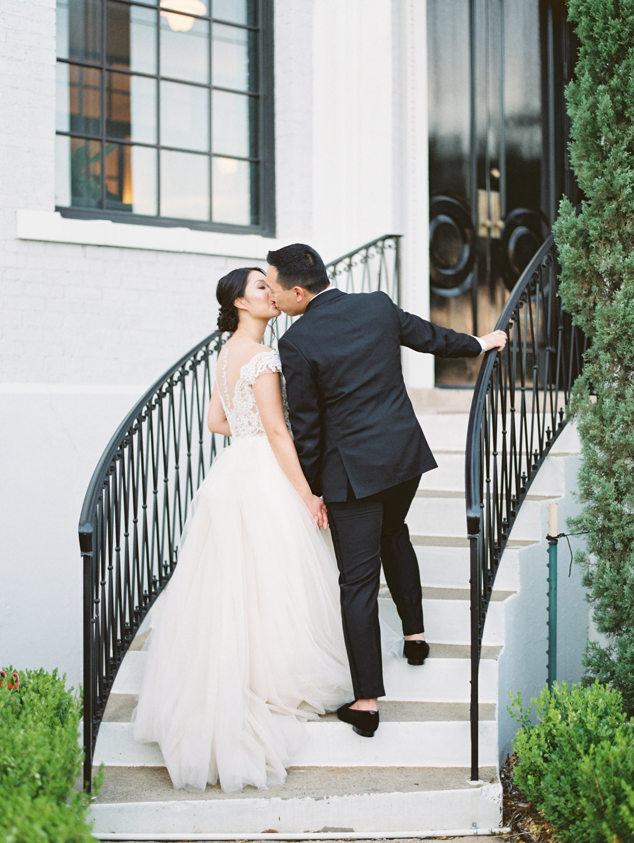 bride and groom kiss outside ascending staircase