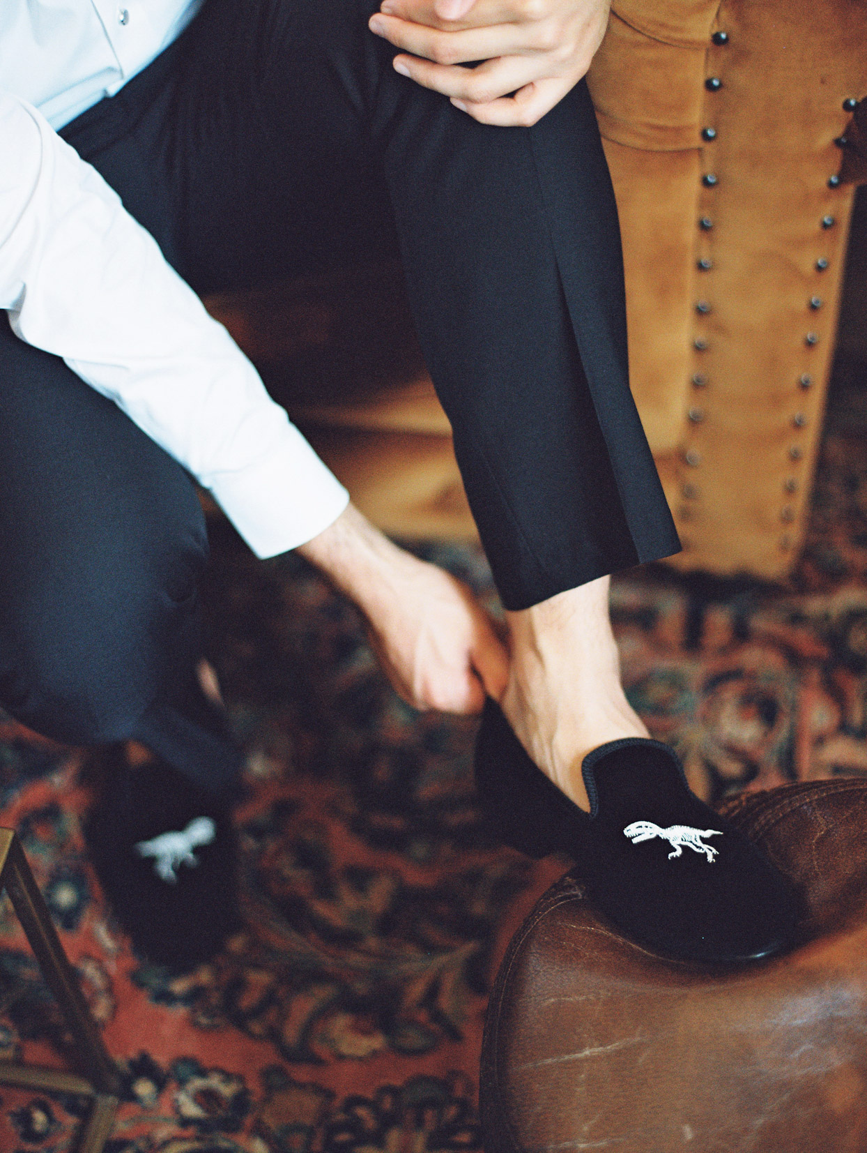 groom wearing embroidered dinosaur shoes