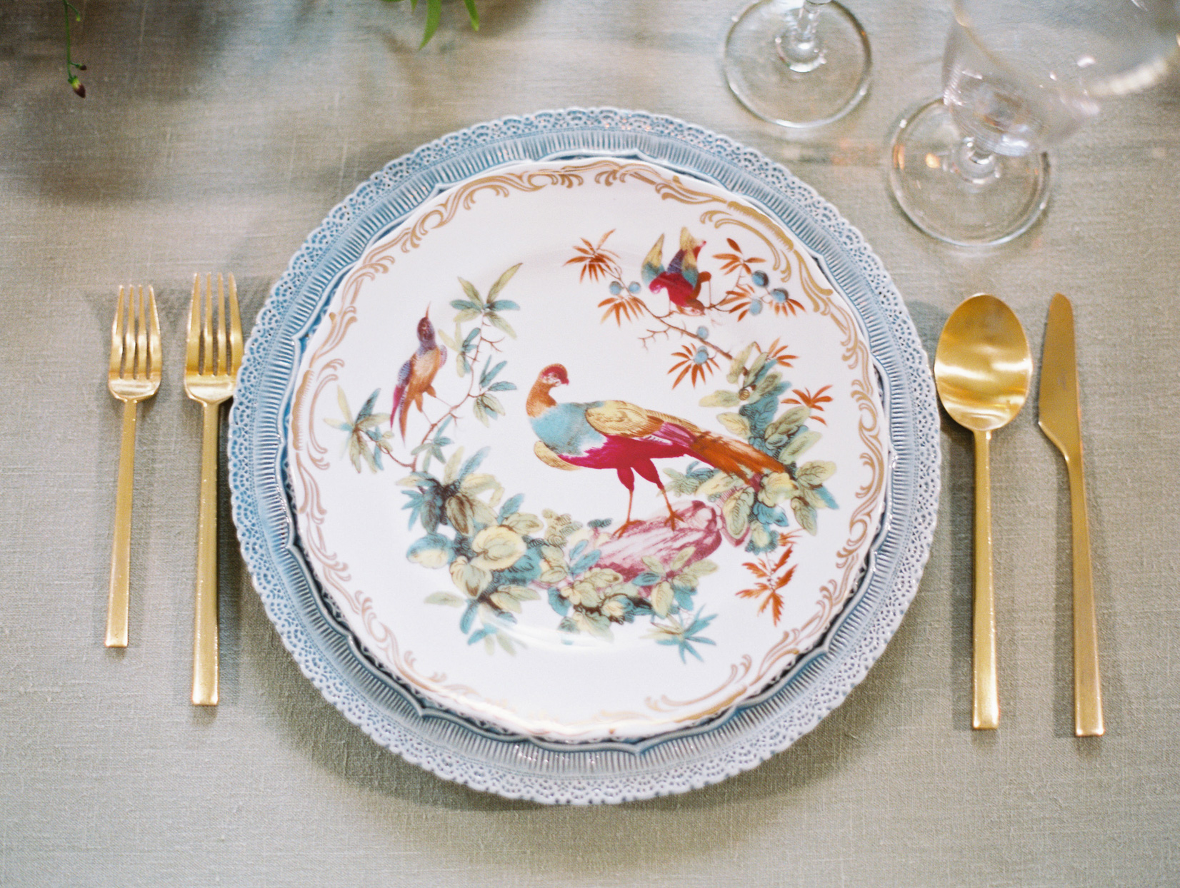 dinner table setting with gold utensils and decorative china plates