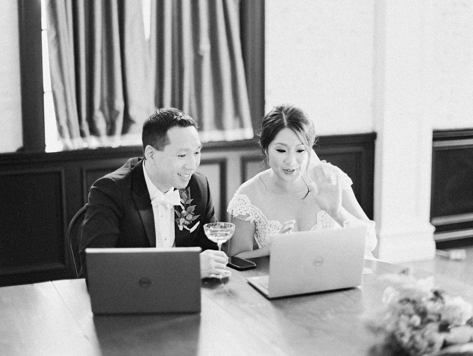 bride and groom seated with cocktails and computers