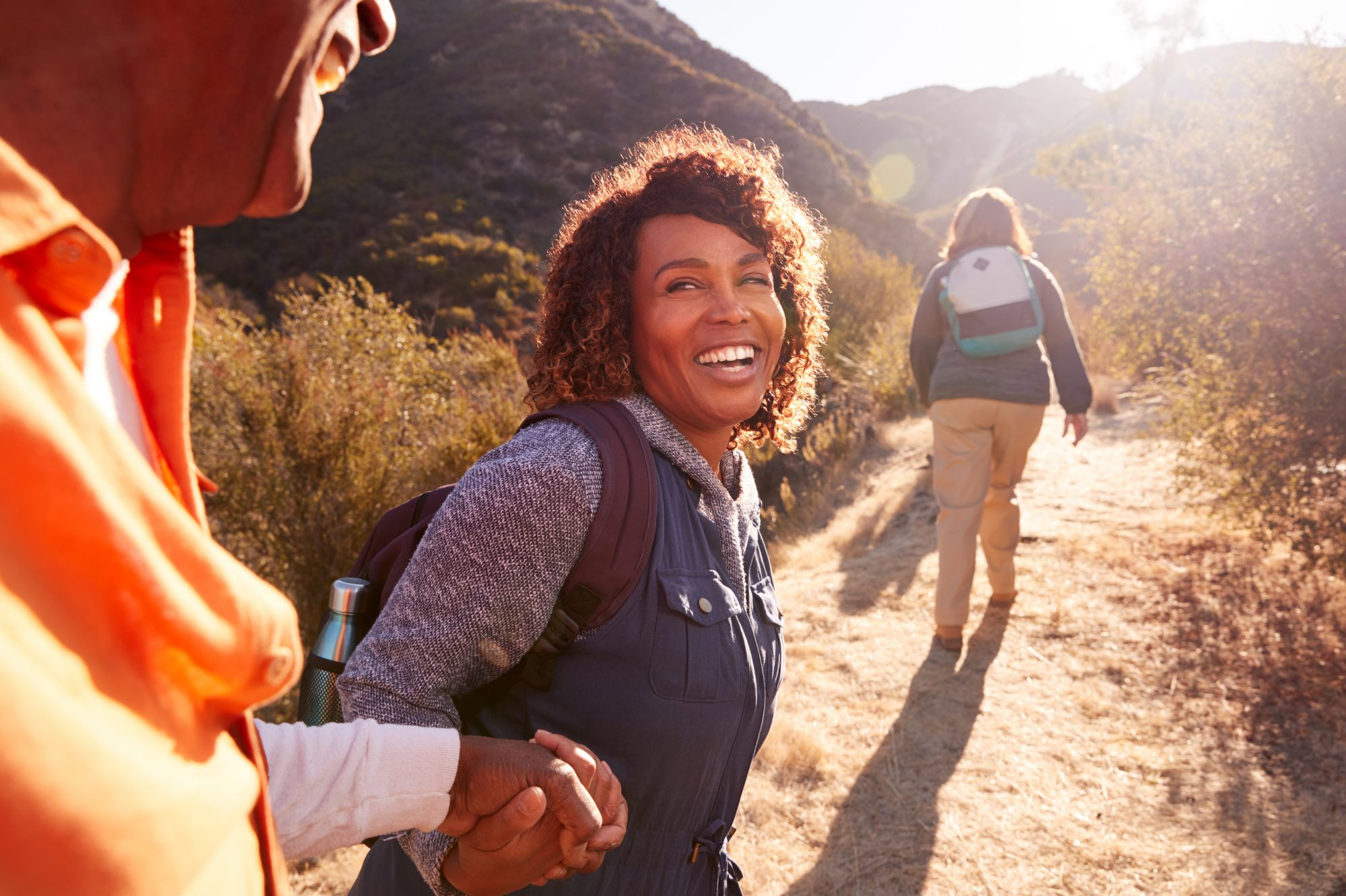 smiling woman hiking on trail