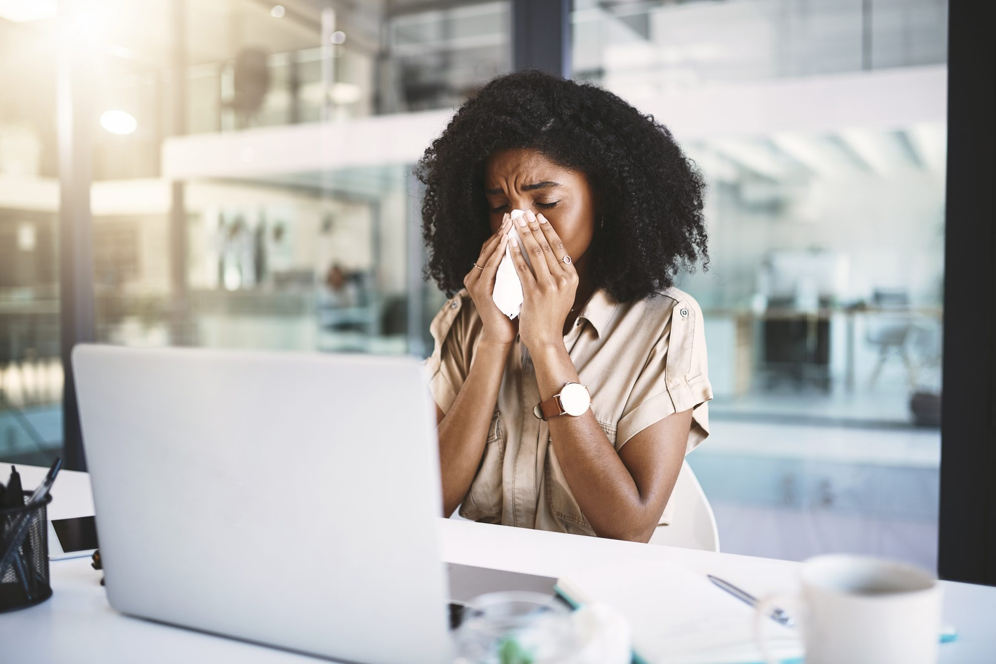 woman sneezing into tissue at desk