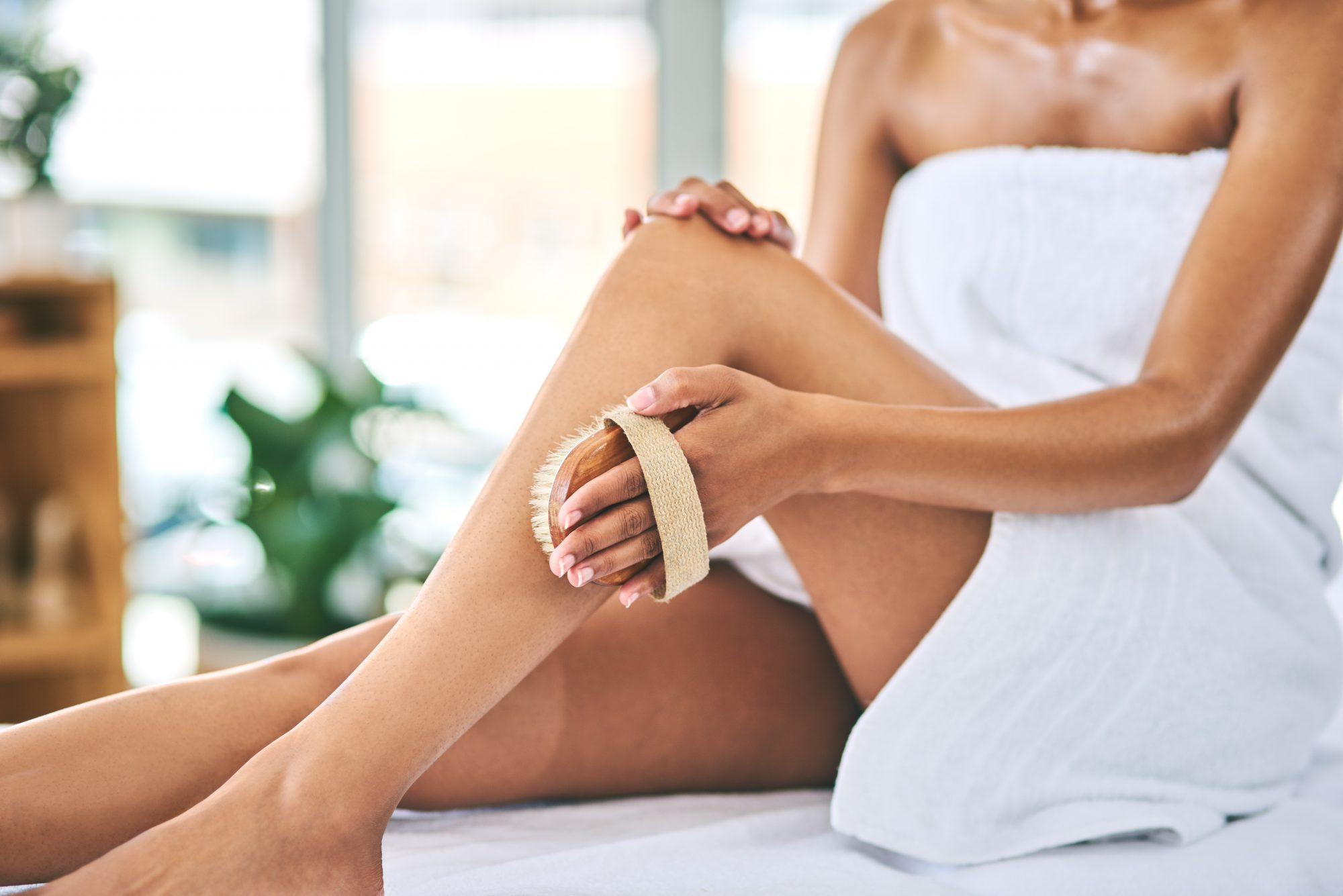 woman exfoliating legs with brush