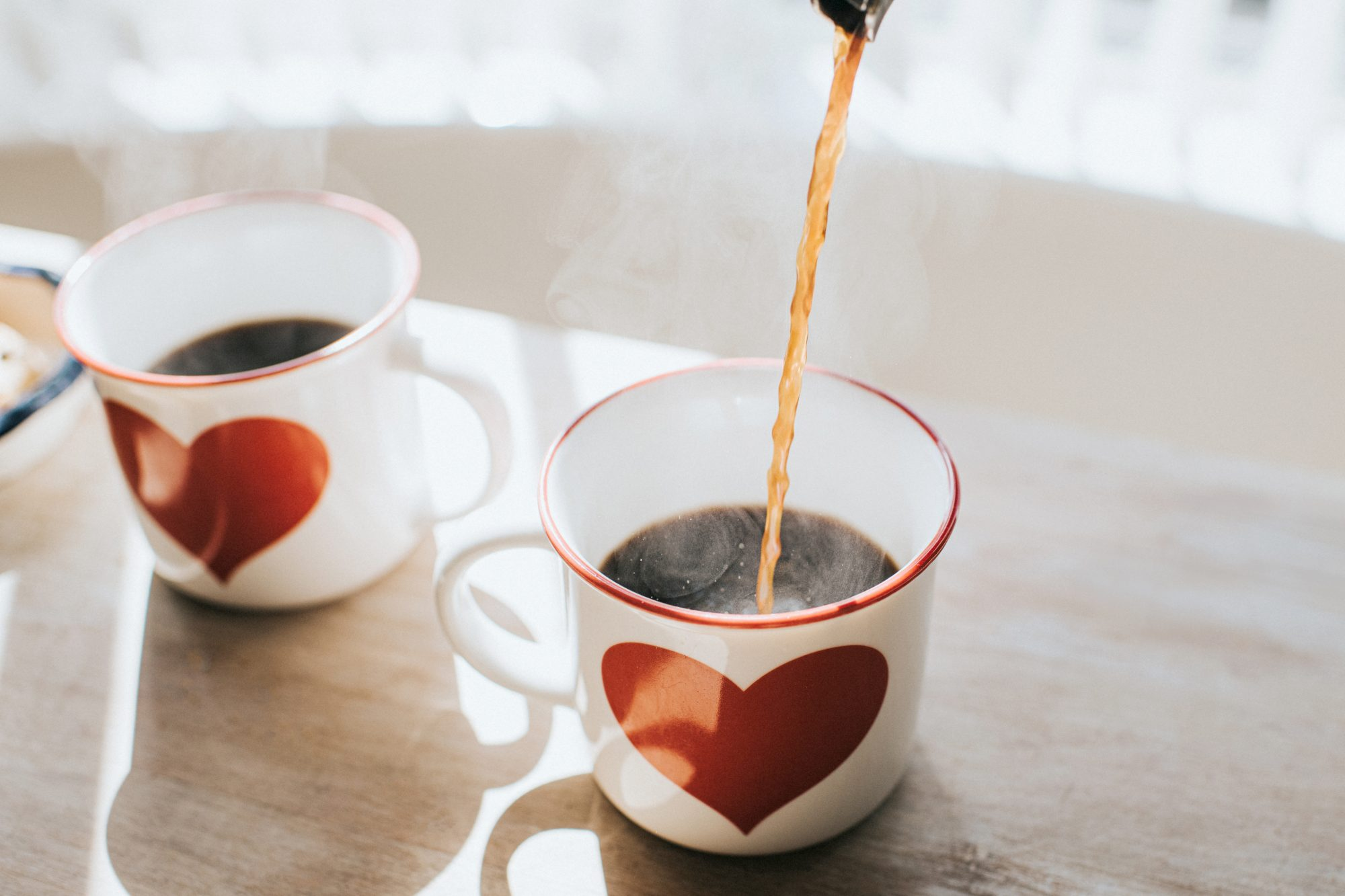 pouring coffee into white mug with heart