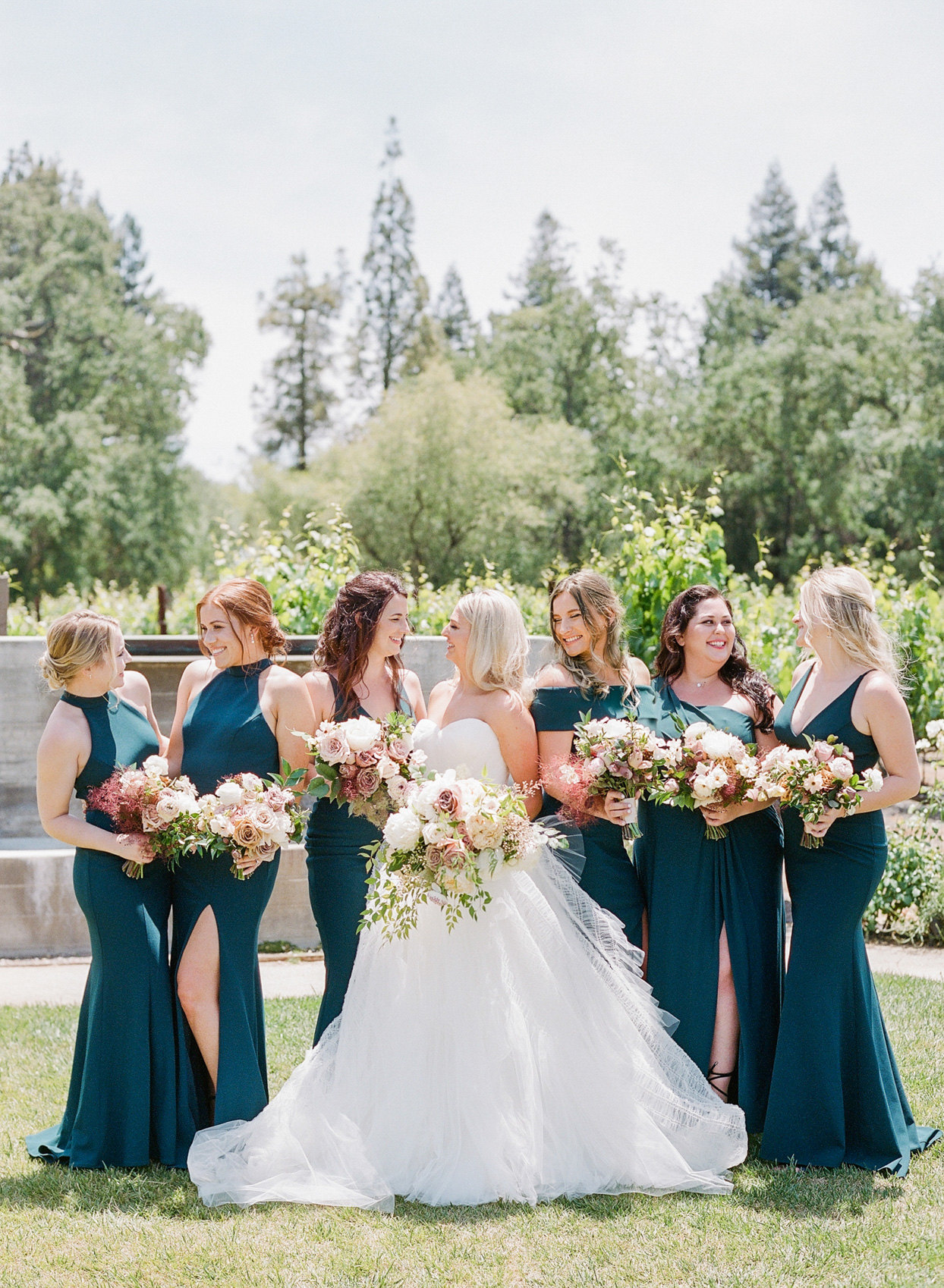 bride with bridesmaids wearing blue-green dresses
