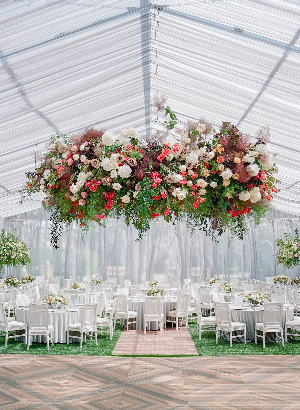 reception tables under canopy set with flowers