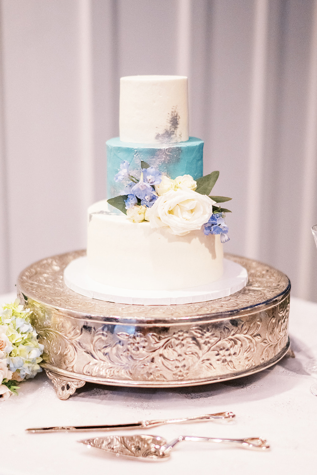 white and blue wedding cake with flowers