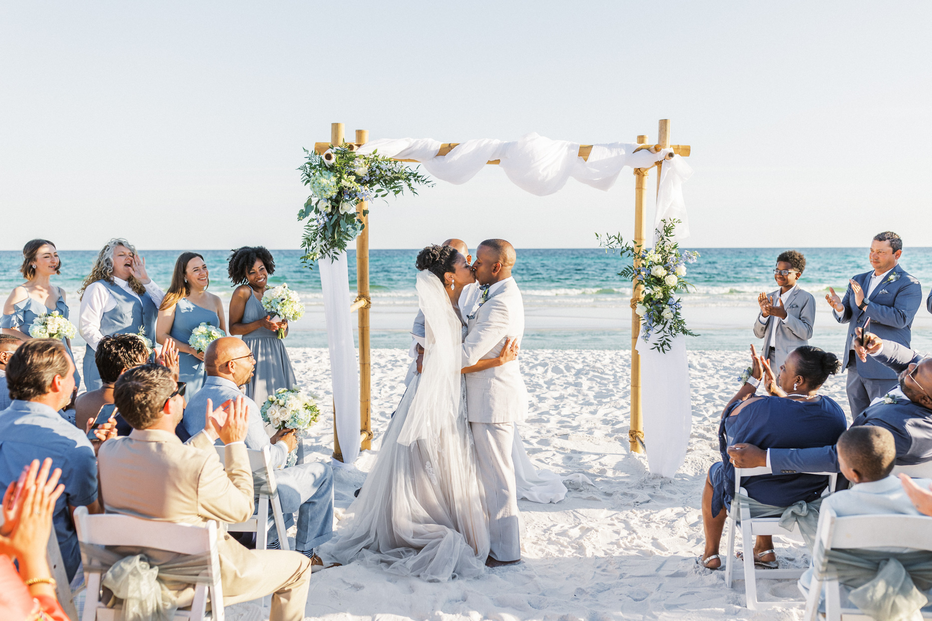 couple kissing at beach wedding ceremony
