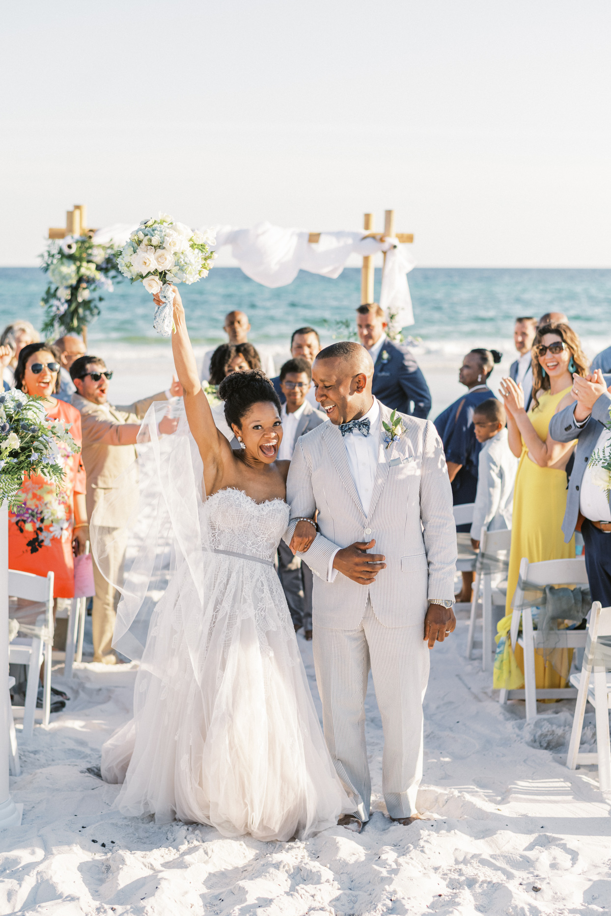 couple celebrating during wedding ceremony recessional on beach