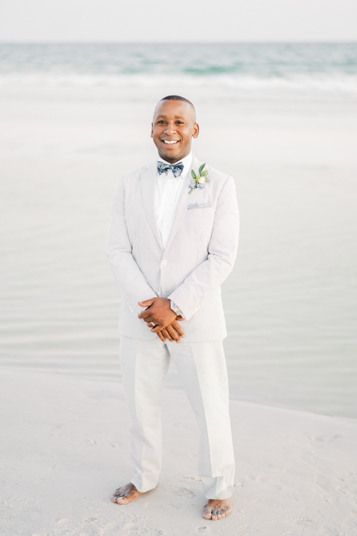 groom in white striped suit standing on beach