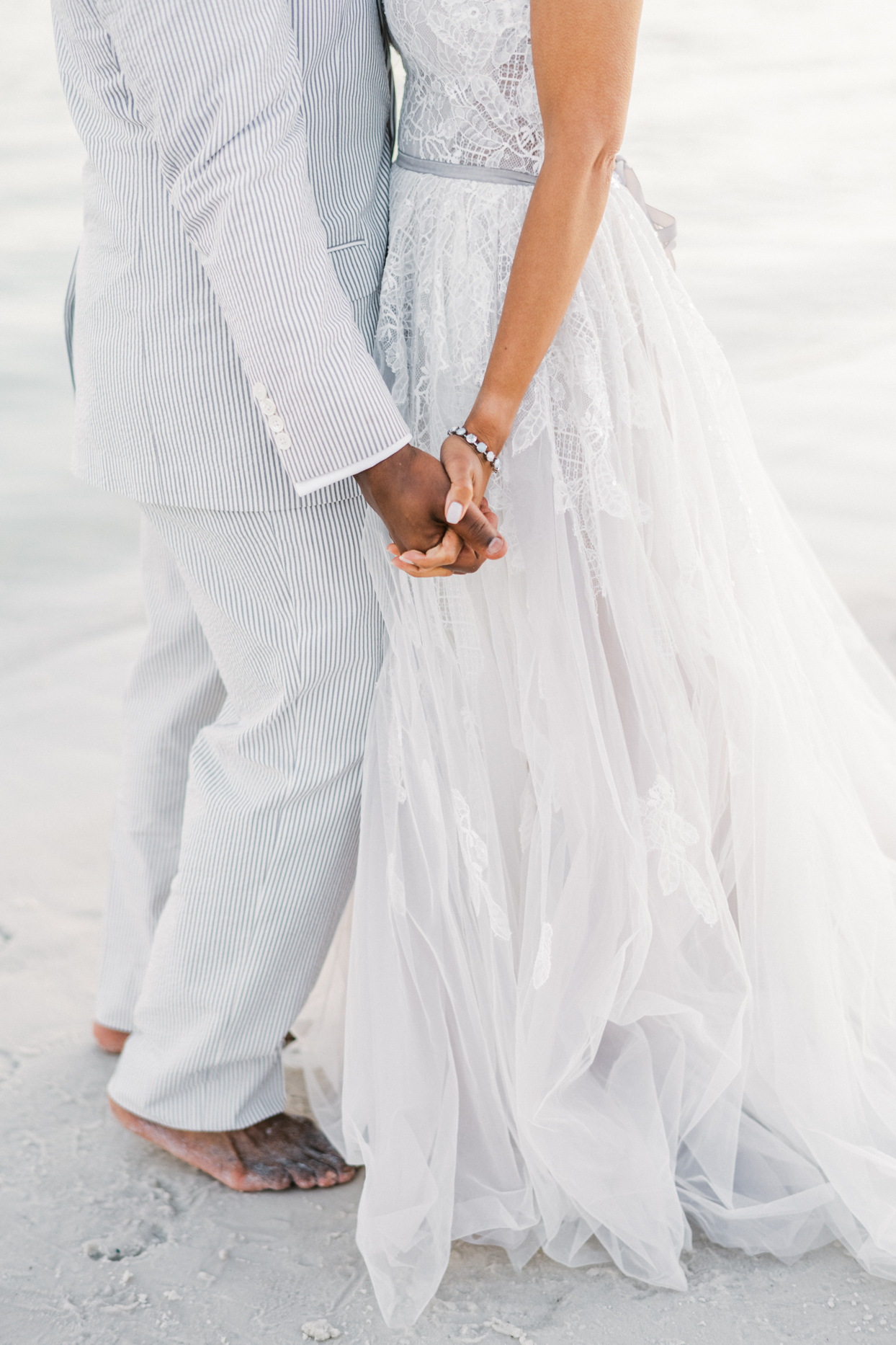 couple holding hands for portrait on beach