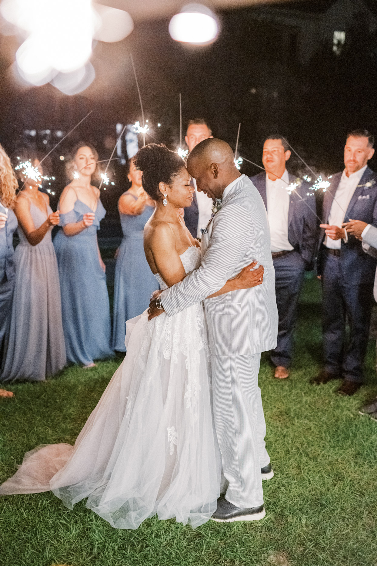 wedding couple embracing while guests hold sparklers