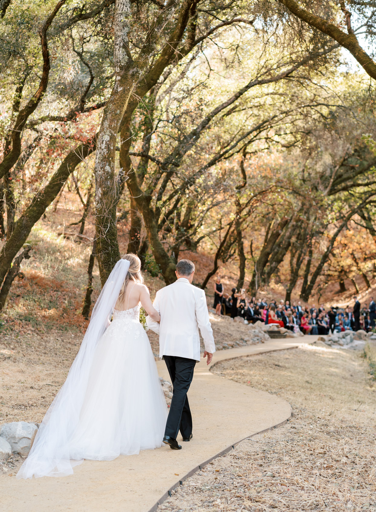 bride and father processing down winding path at wedding ceremony