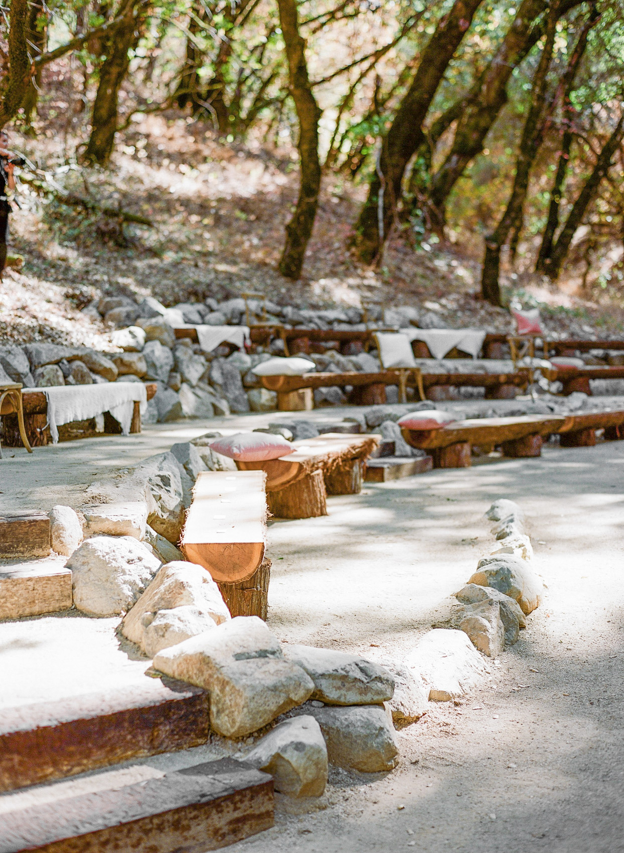 rustic outdoor wedding ceremony rock and wooden benches