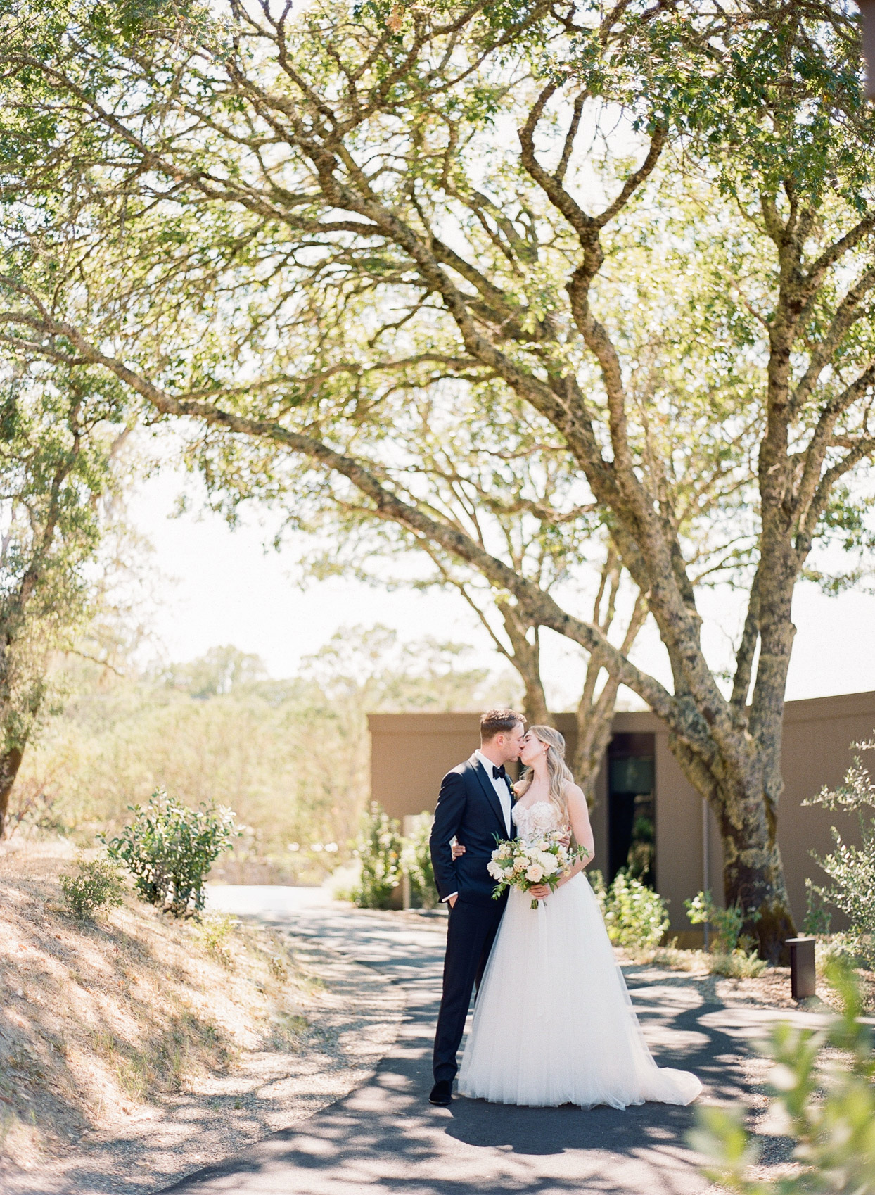 couple kissing on outdoor path