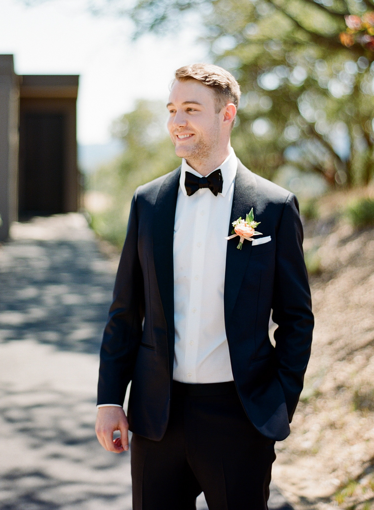 groom in black suit with pale pink boutonniere