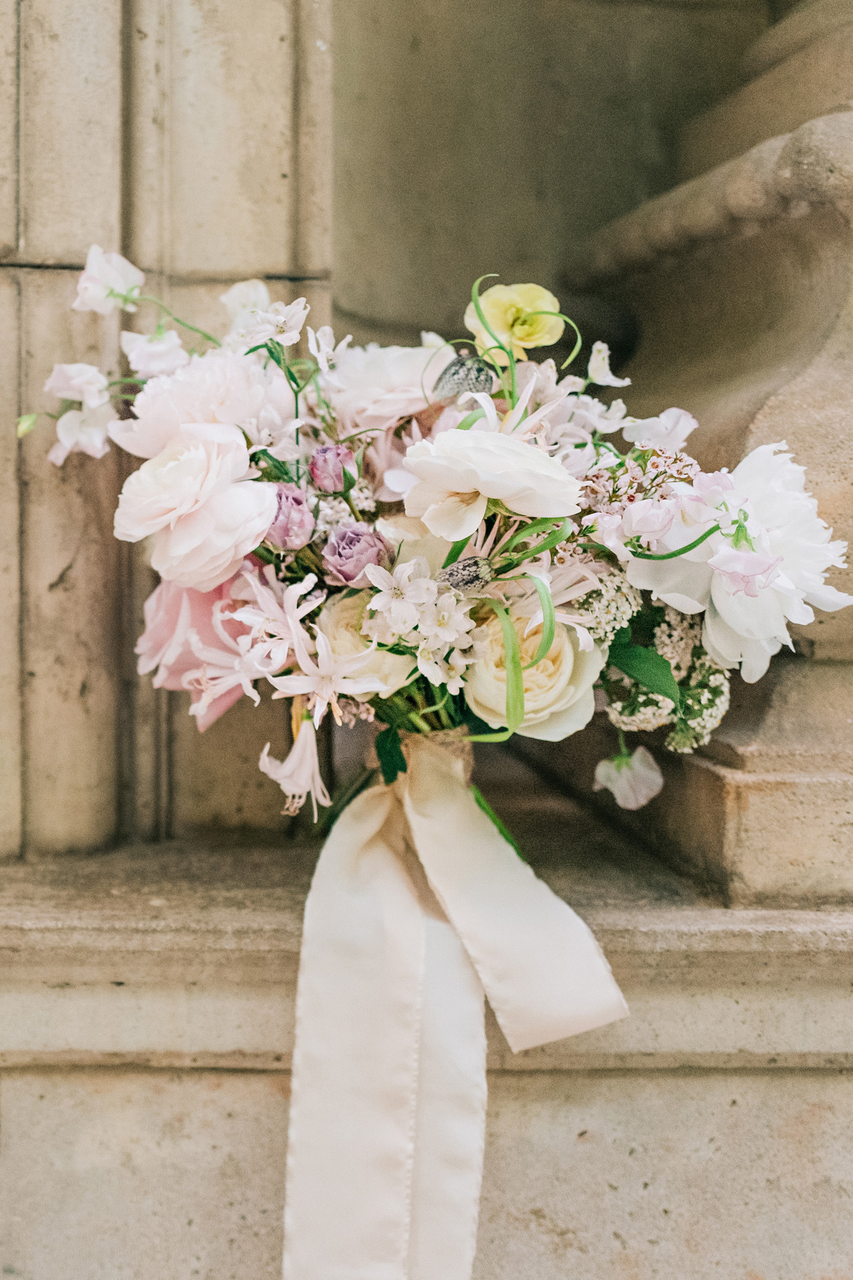 asymmetrical organic bridal bouquet of peonies sweet pea and garden roses