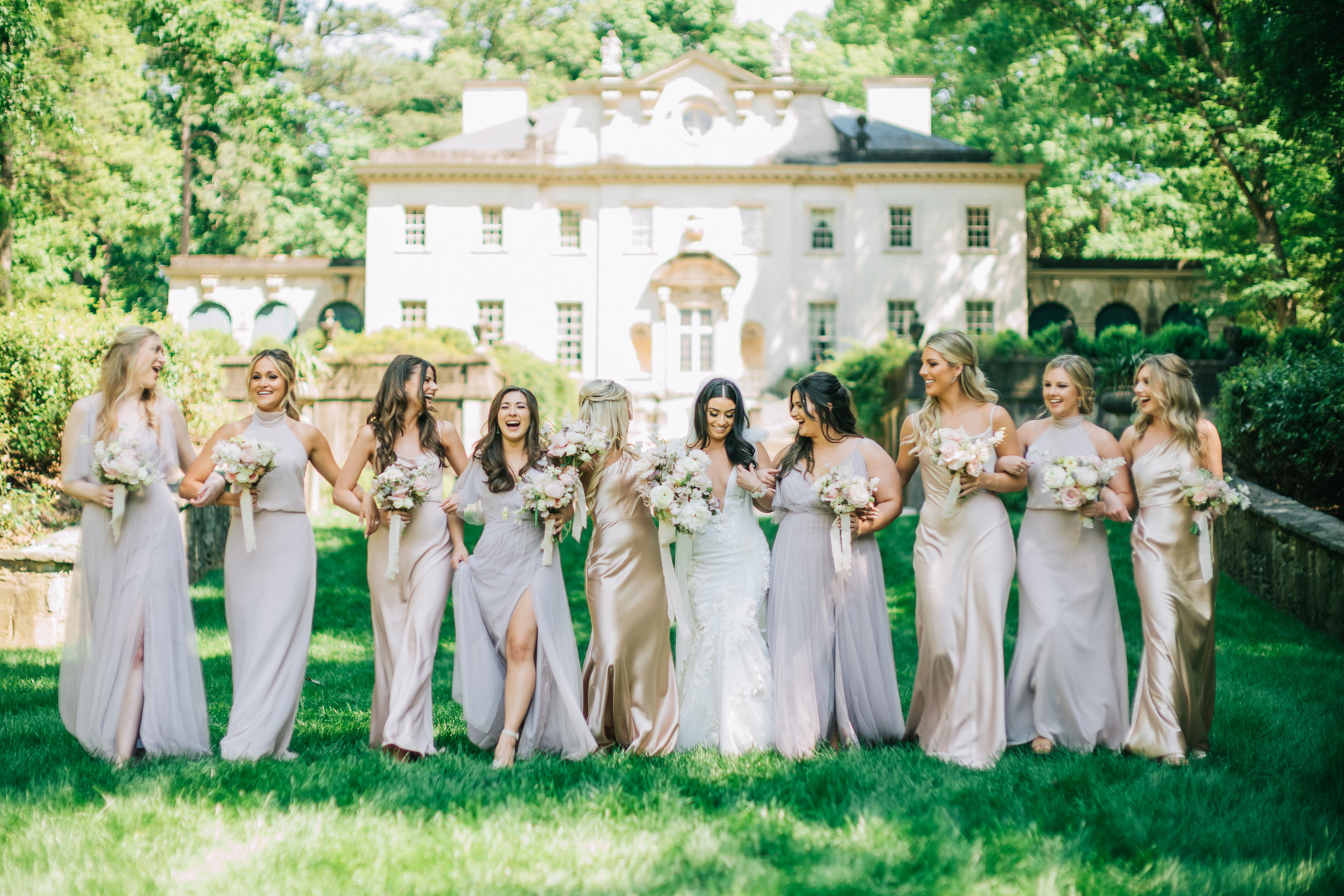 bride with bridesmaids wearing varying styles in shades of blush mauve and champagne