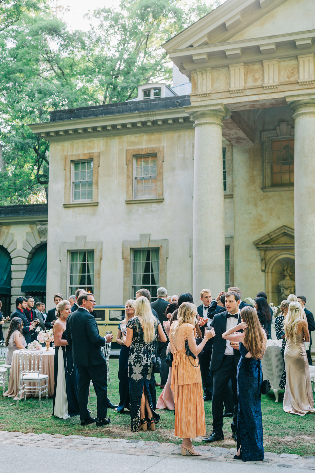 wedding guests enjoying cocktail outside historic property