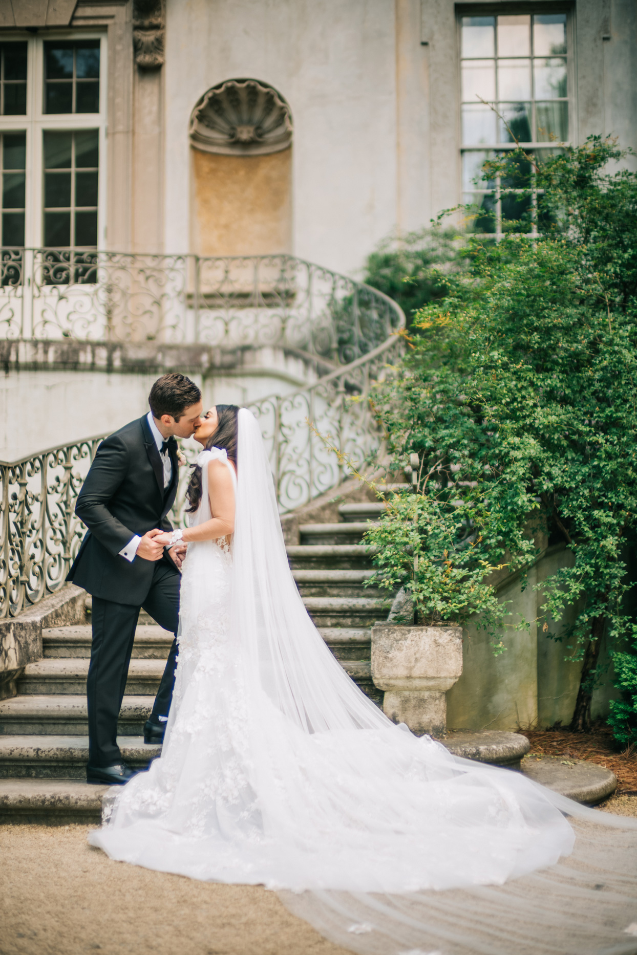 bride and groom kissing on stairs of wedding venue