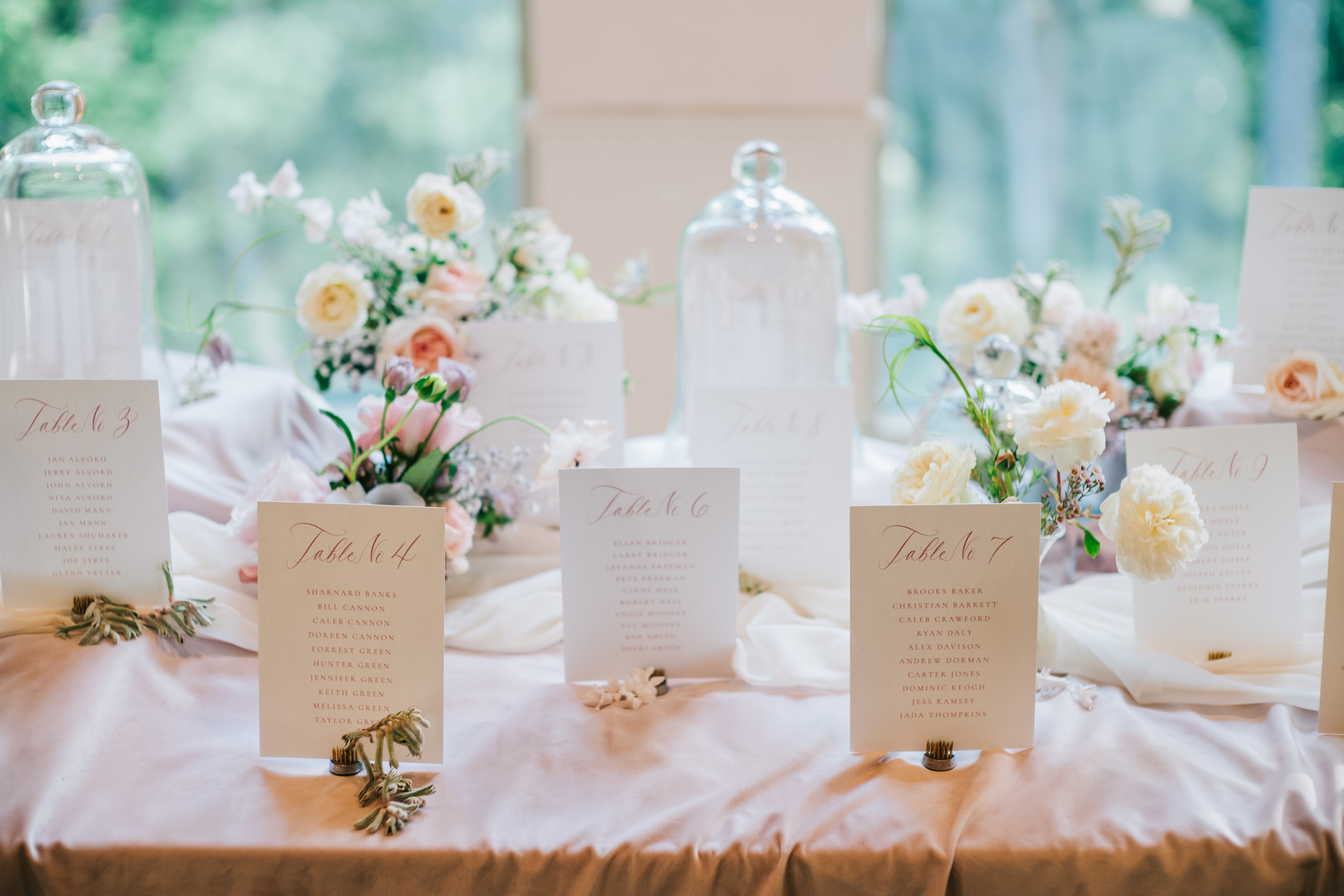 escort card table with flowers and glass cloches