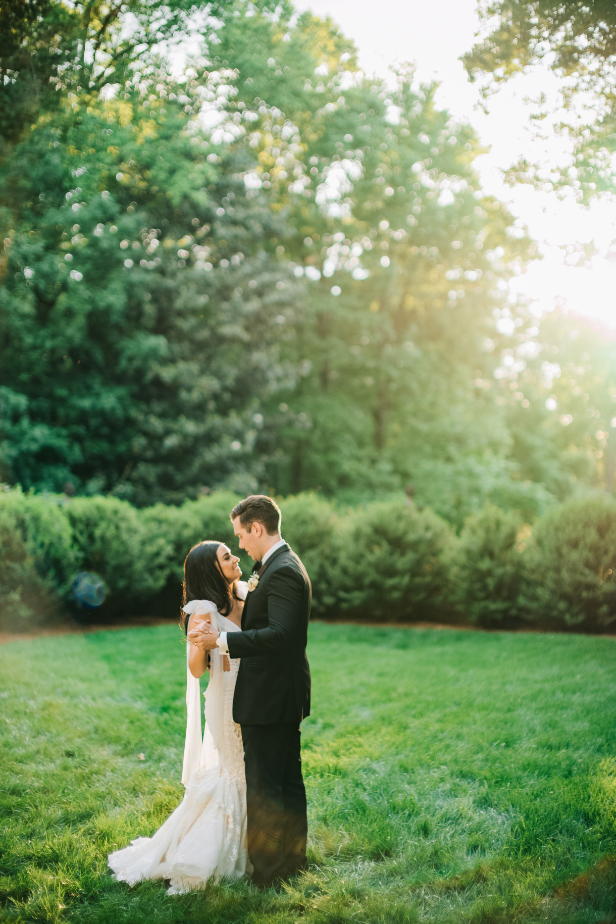 bride and groom embracing on venue lawn