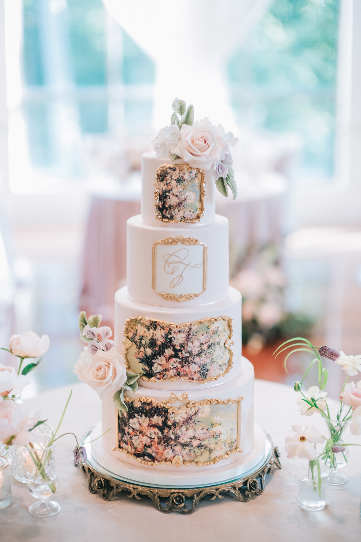 blush four-tier wedding cake embellished with gold filigree and monet painting