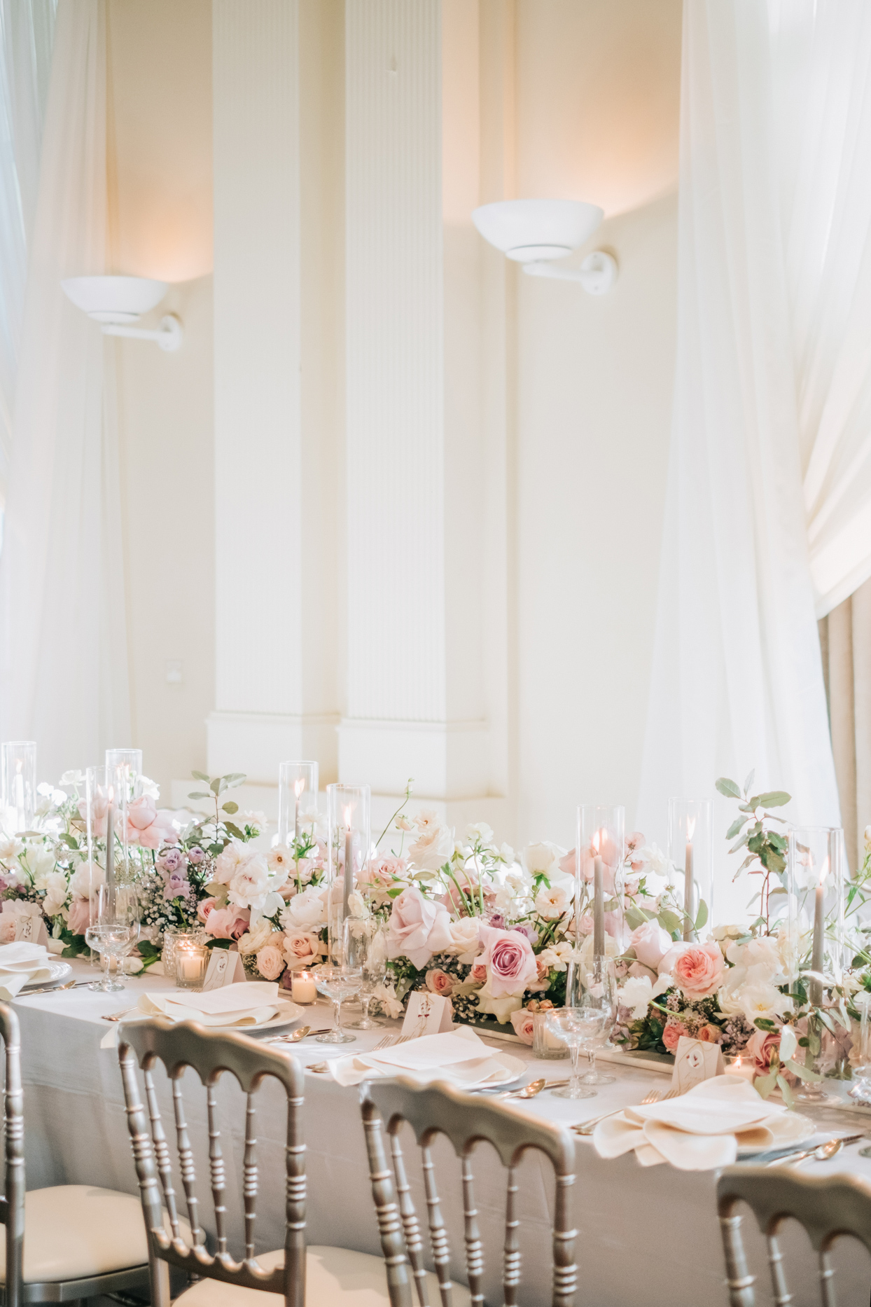 wedding reception centerpieces featuring blush and cream florals and taper candles in glass hurricanes
