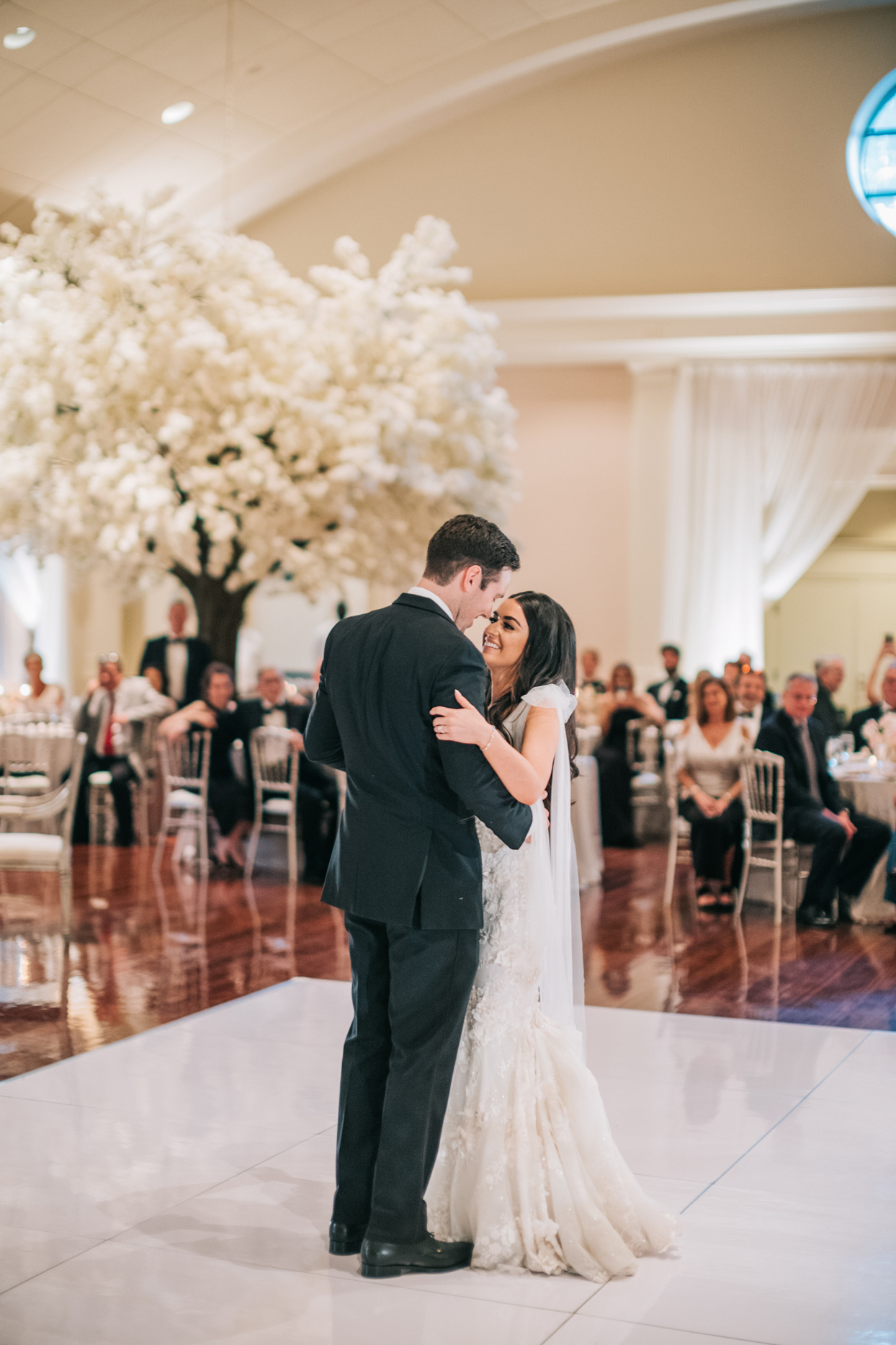 bride and groom smiling while sharing first dance