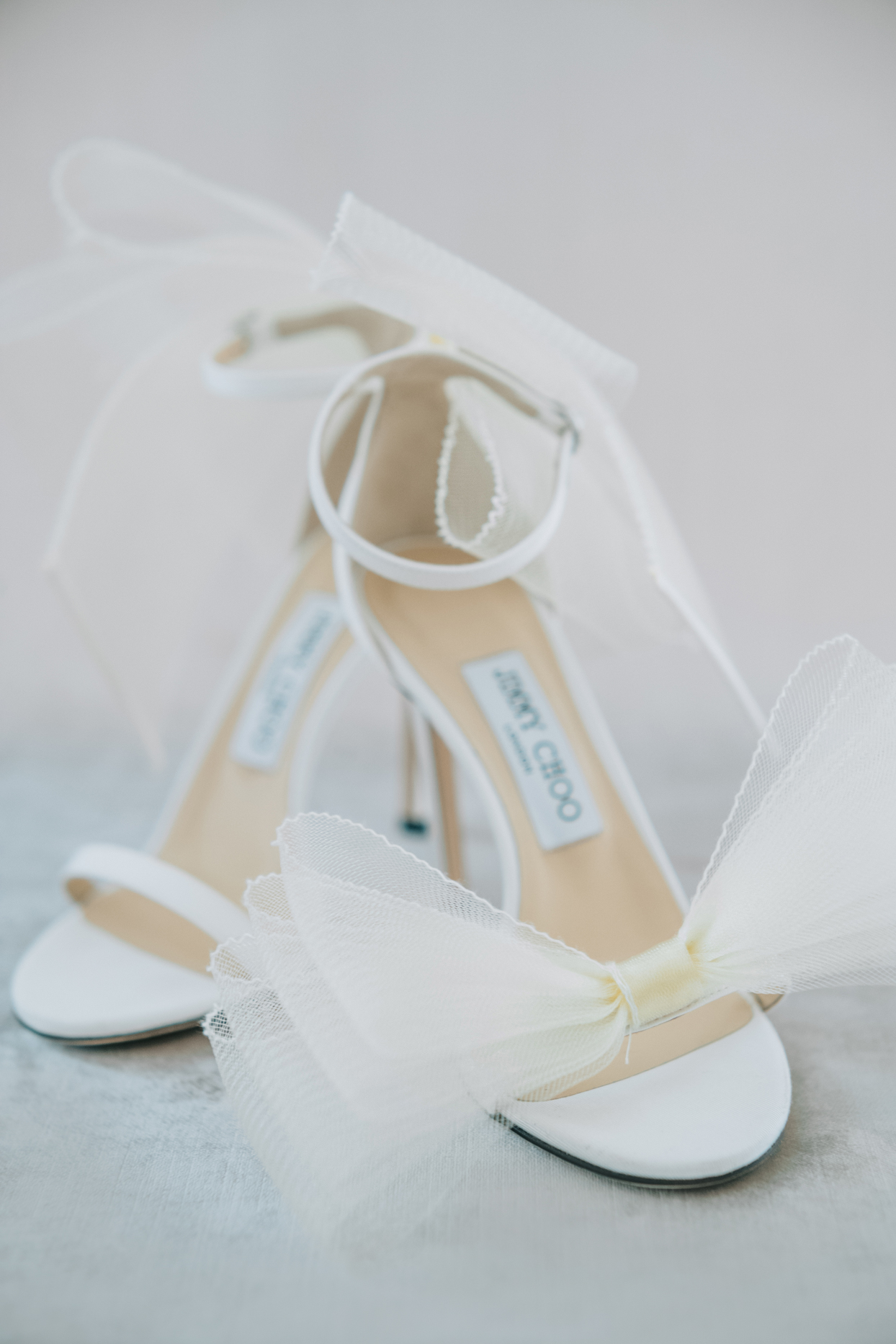 white jimmy choo shoes with bow details