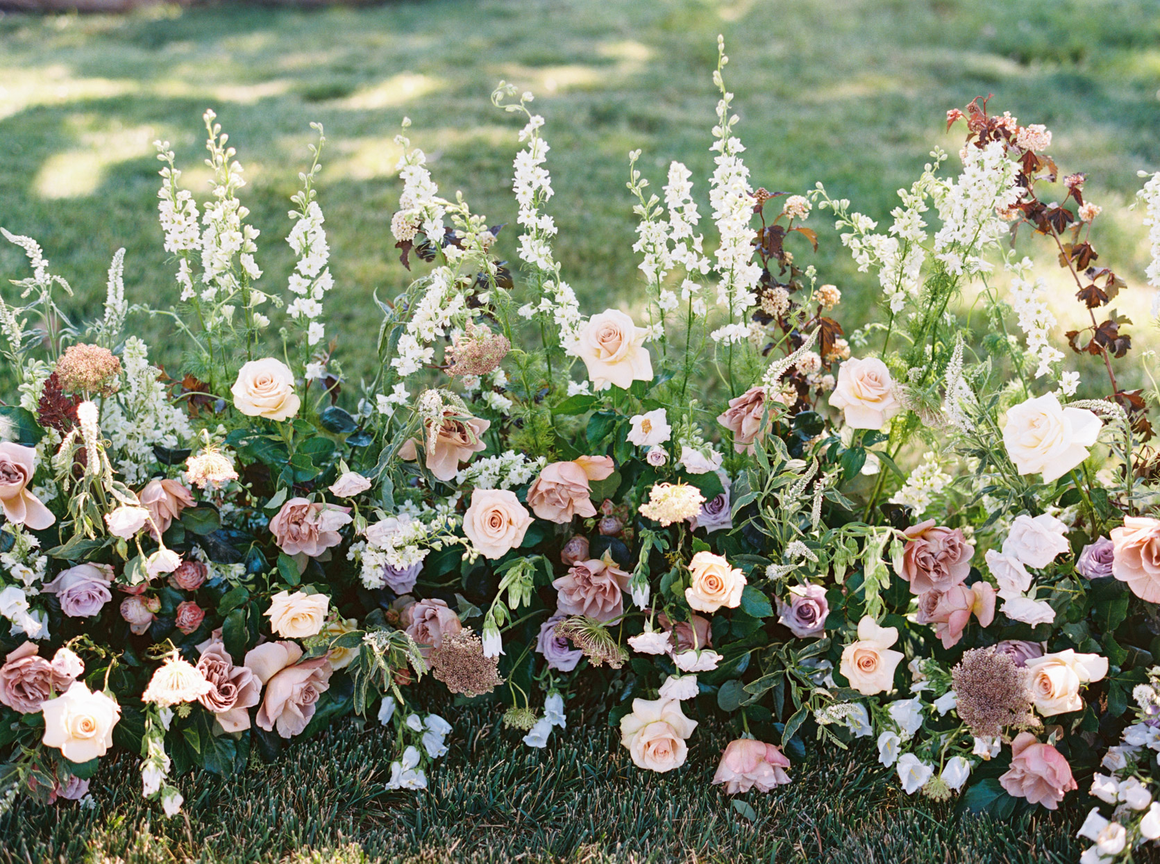 pink and burgundy and cream colored wedding ceremony floral arch