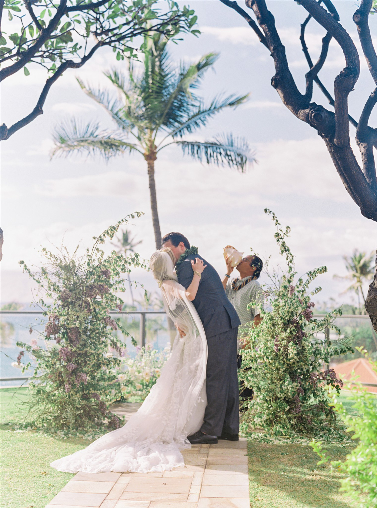 officiant blowing on conch shell bride and groom sharing kiss