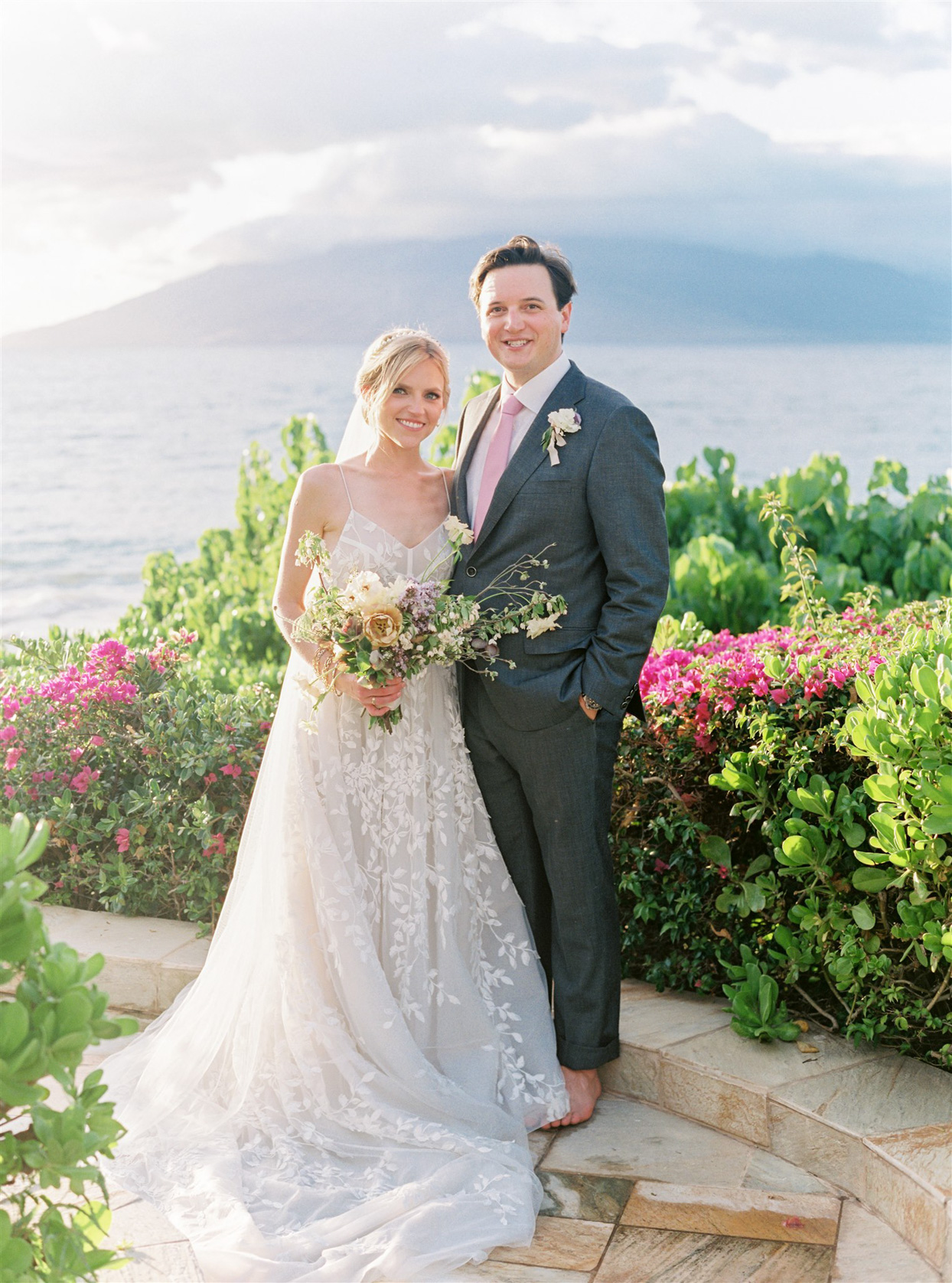 bride and groom posing in front of ocean surrounded by pink flowers
