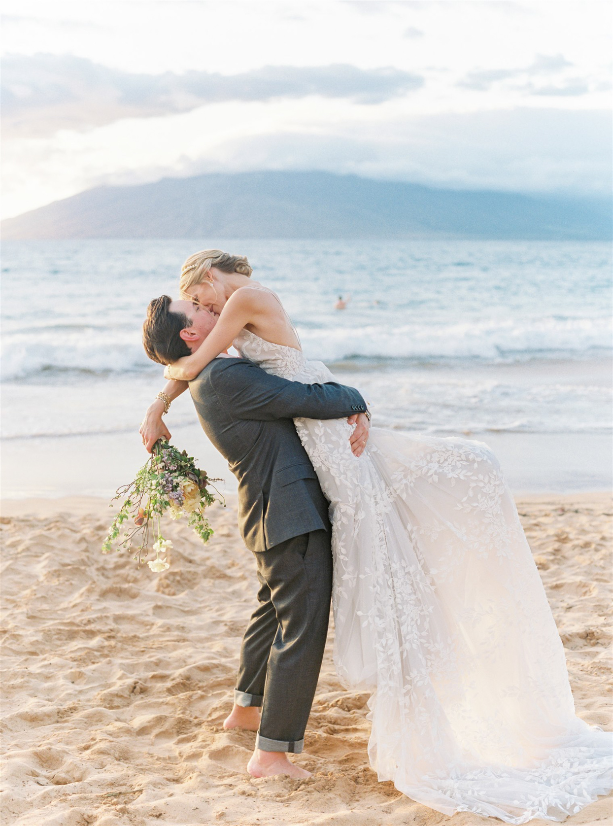 groom picking up bride and kissing her on beach